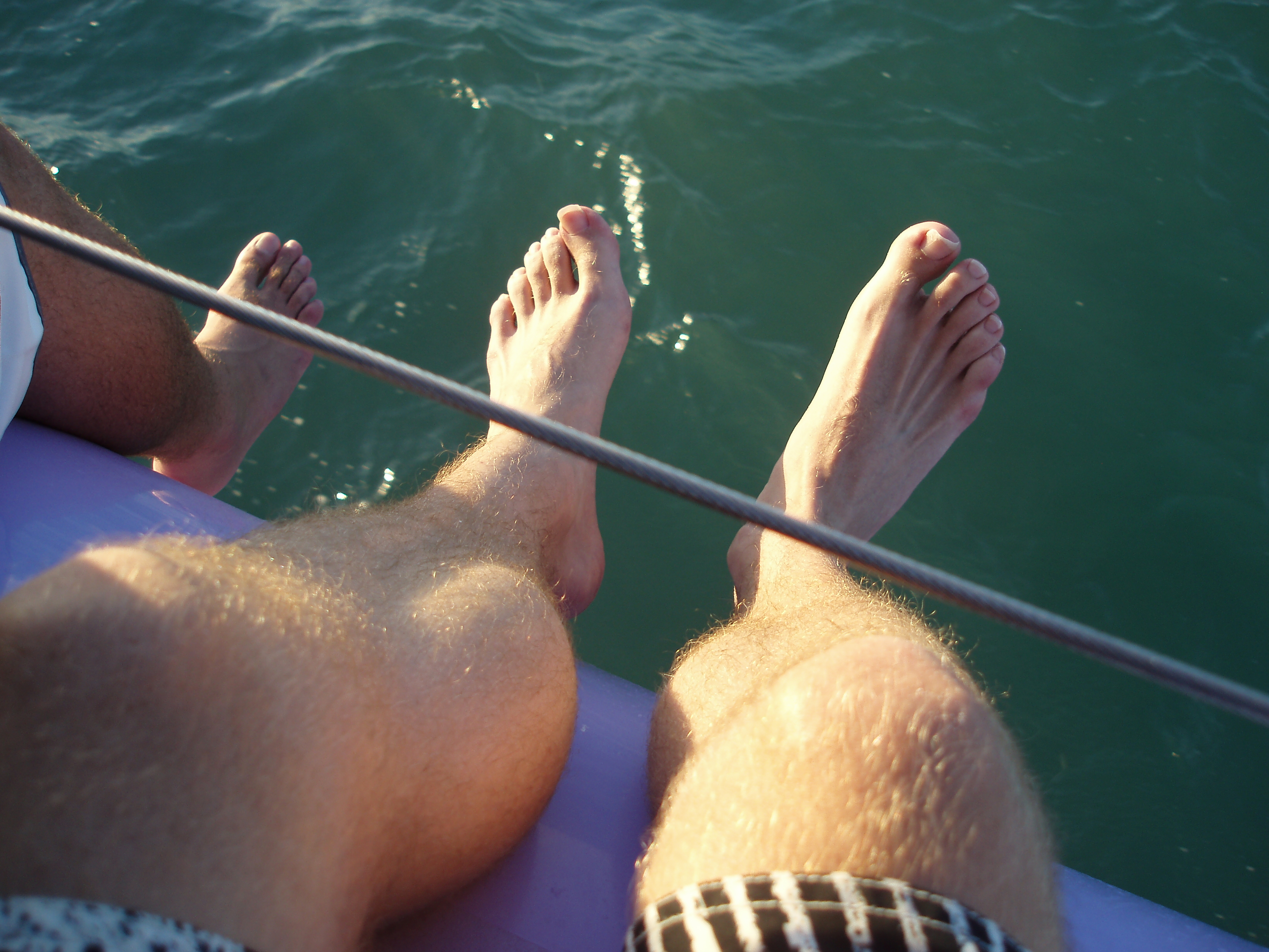 legs hanging over the side of a boat