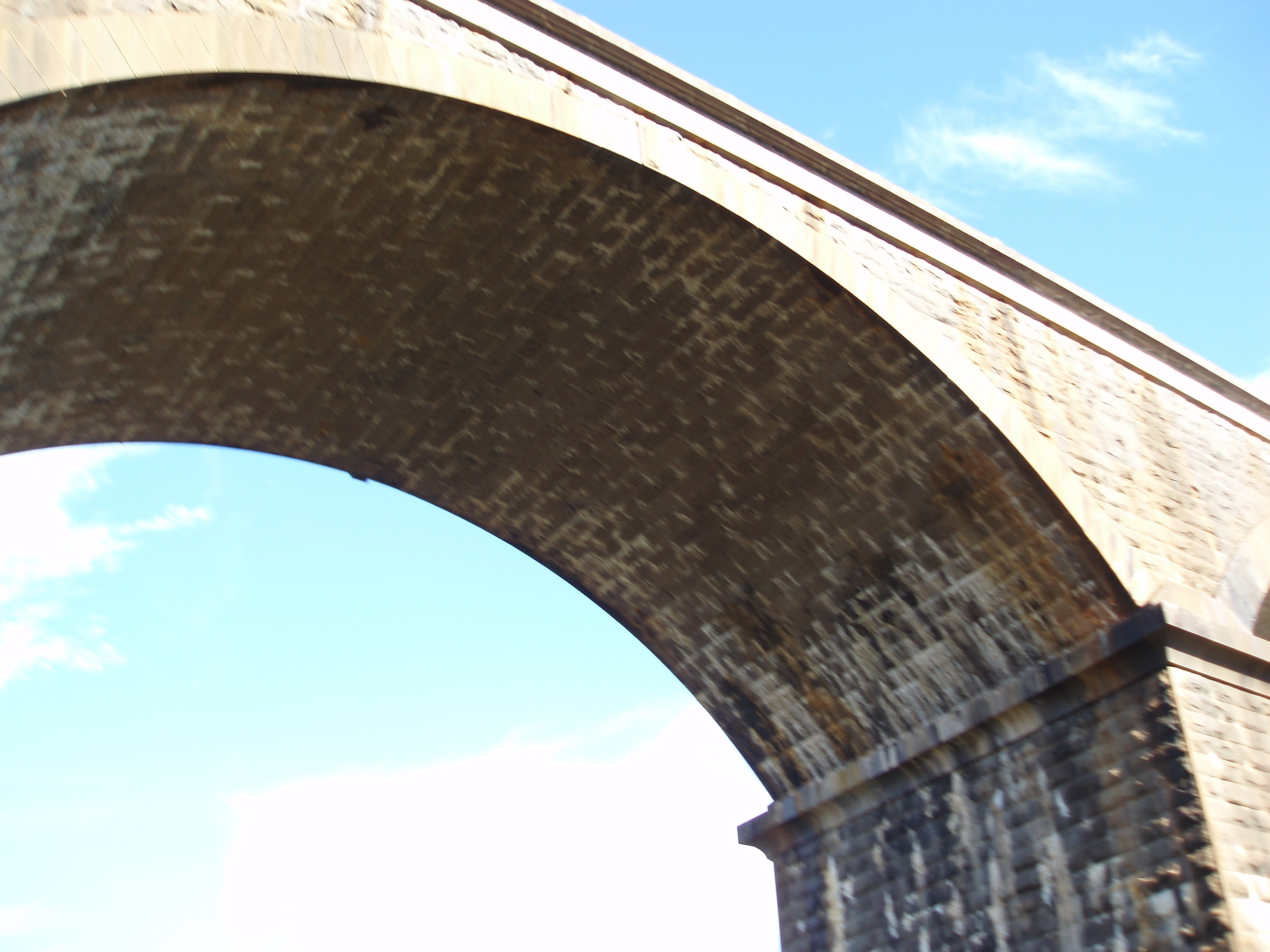overexposed image of a railway viaduct stone arch