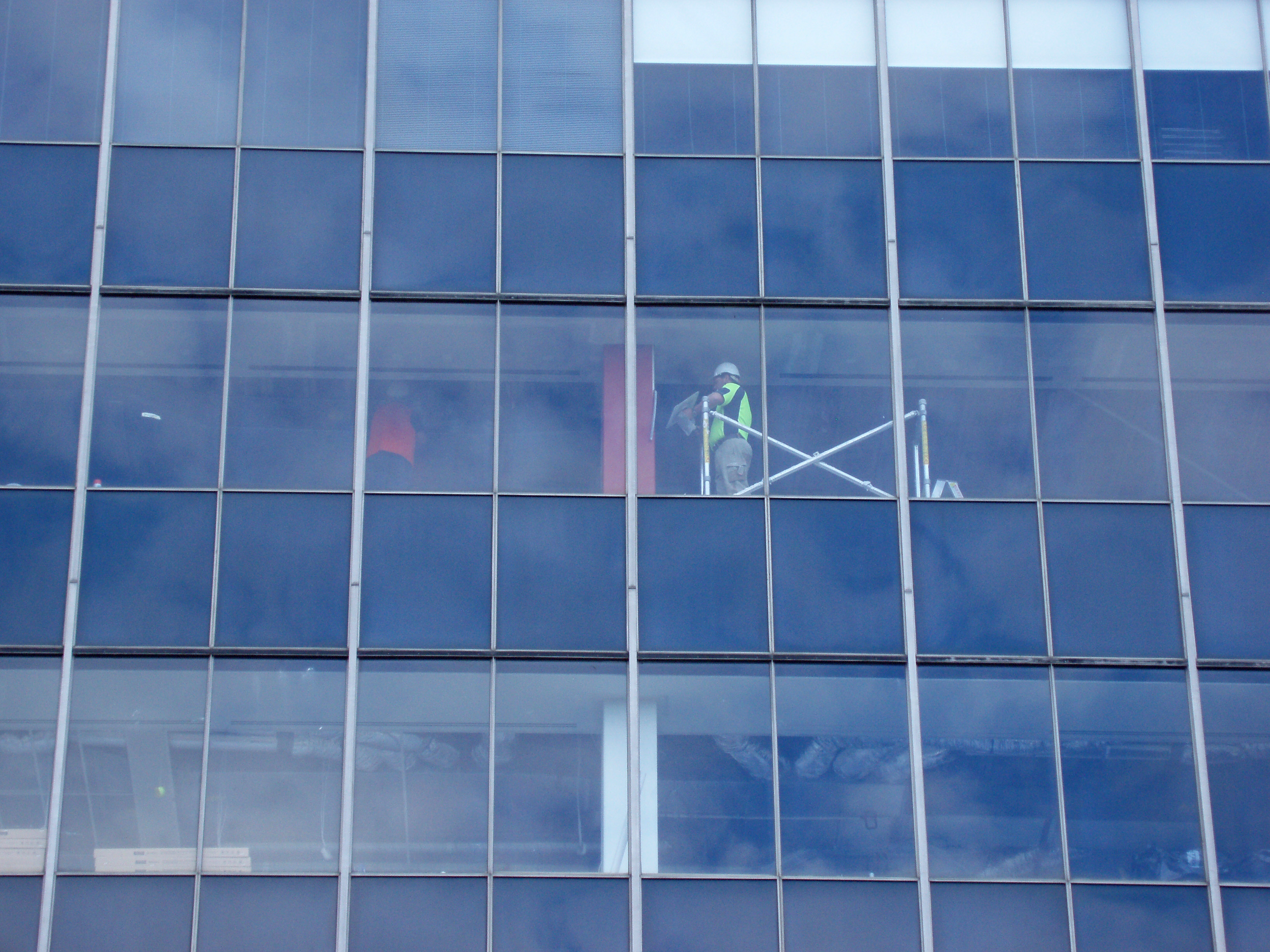 workers behind glass, modern office building redecoration