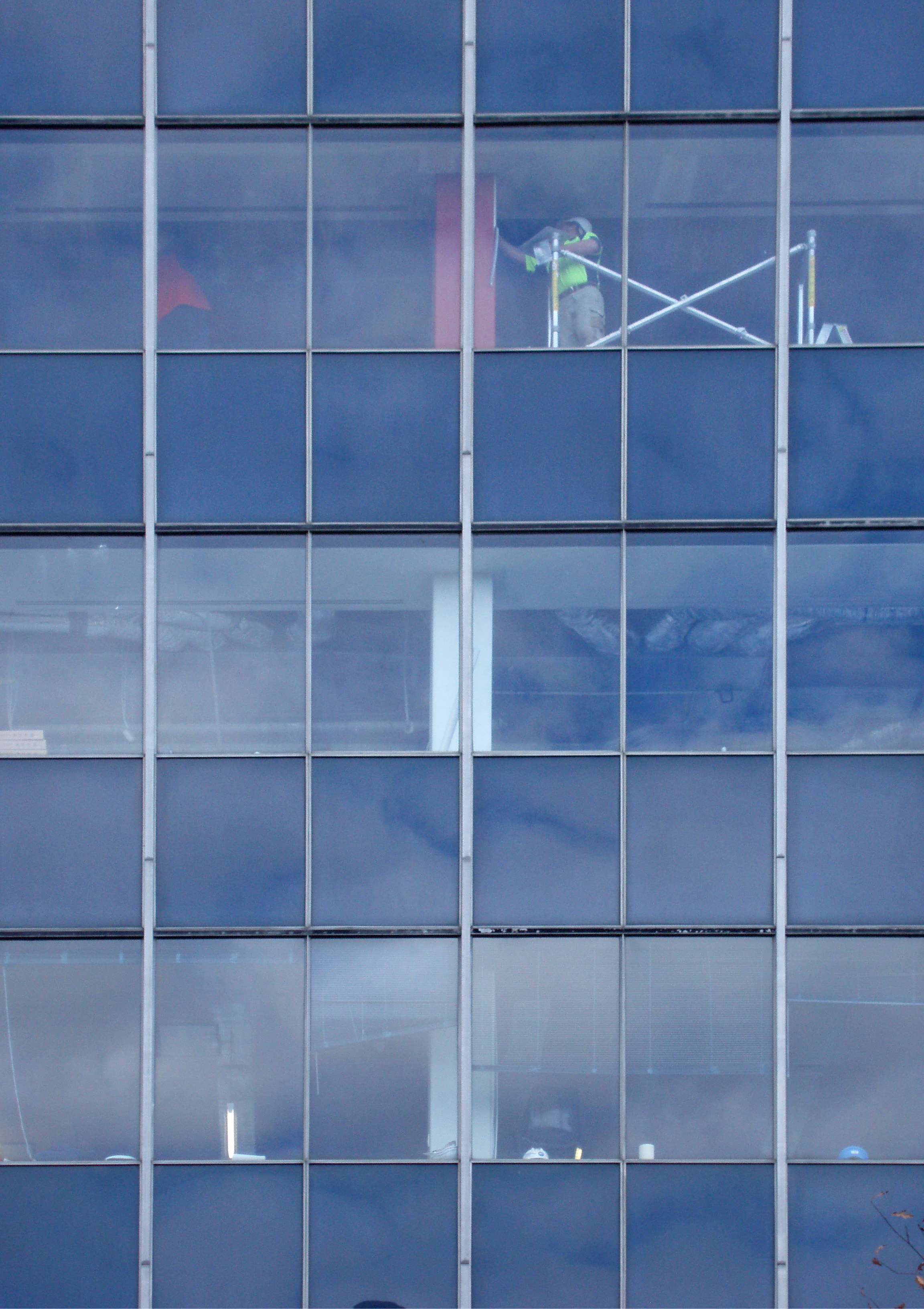 workers behind glass in a modern office building redecoration