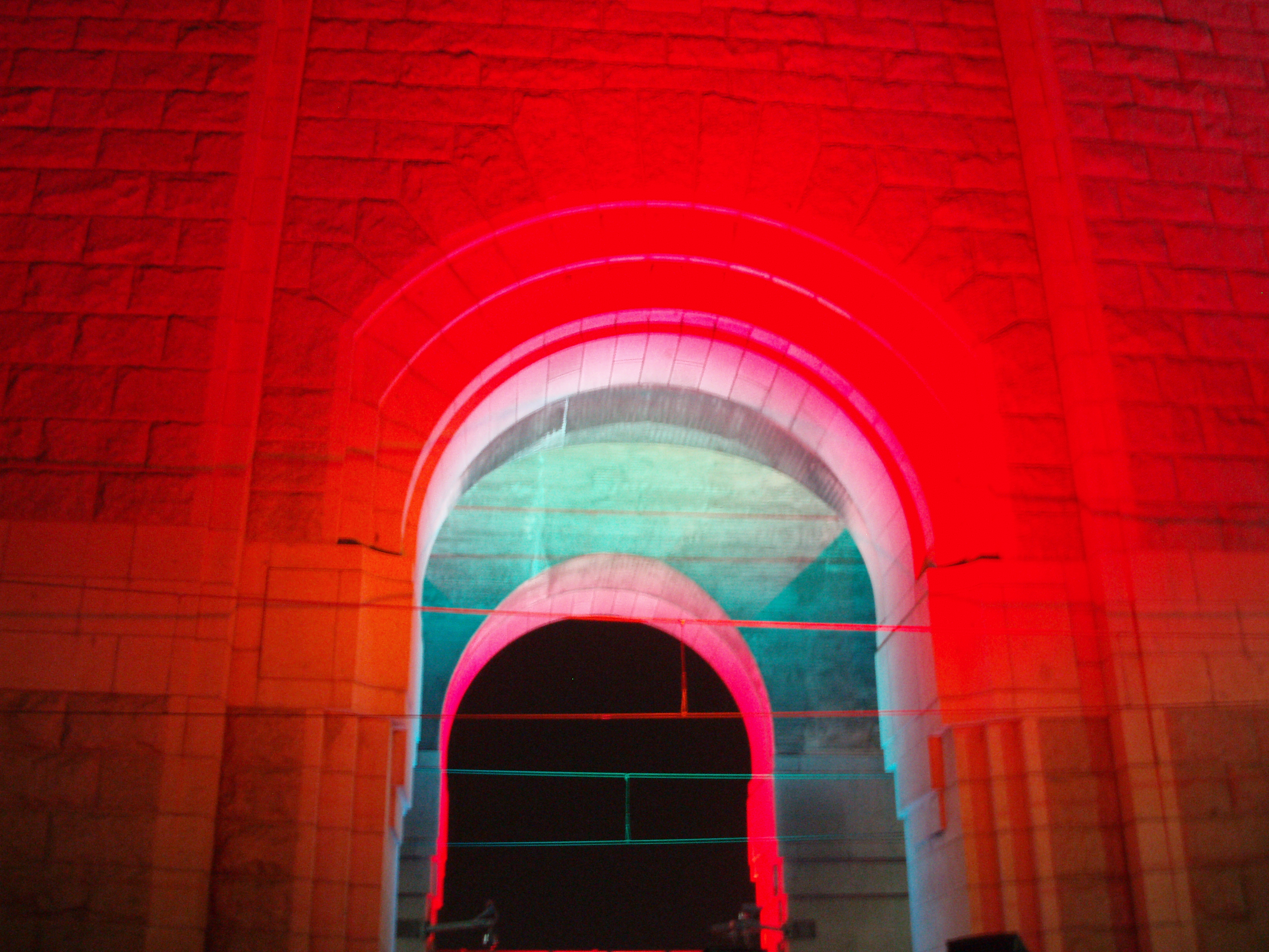 stone arch illuminated by brightly coloured lights