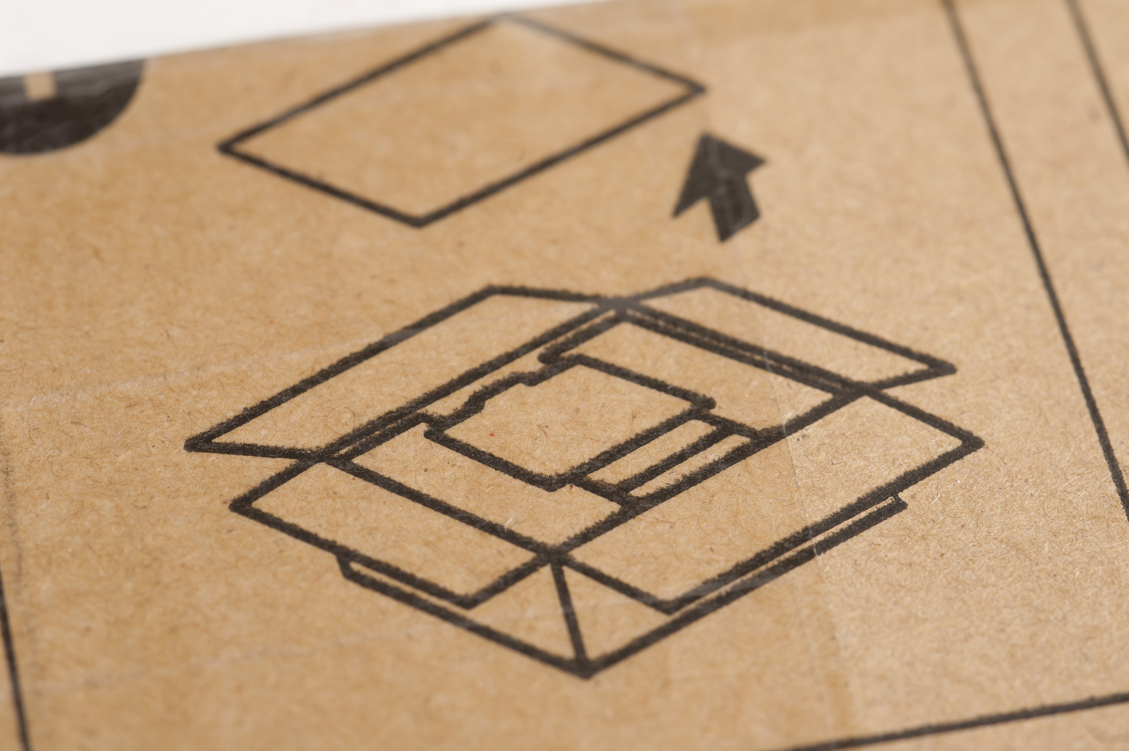 Operating instructions for packaging stamped on a brown cardboard box with a diagram showing how to open it