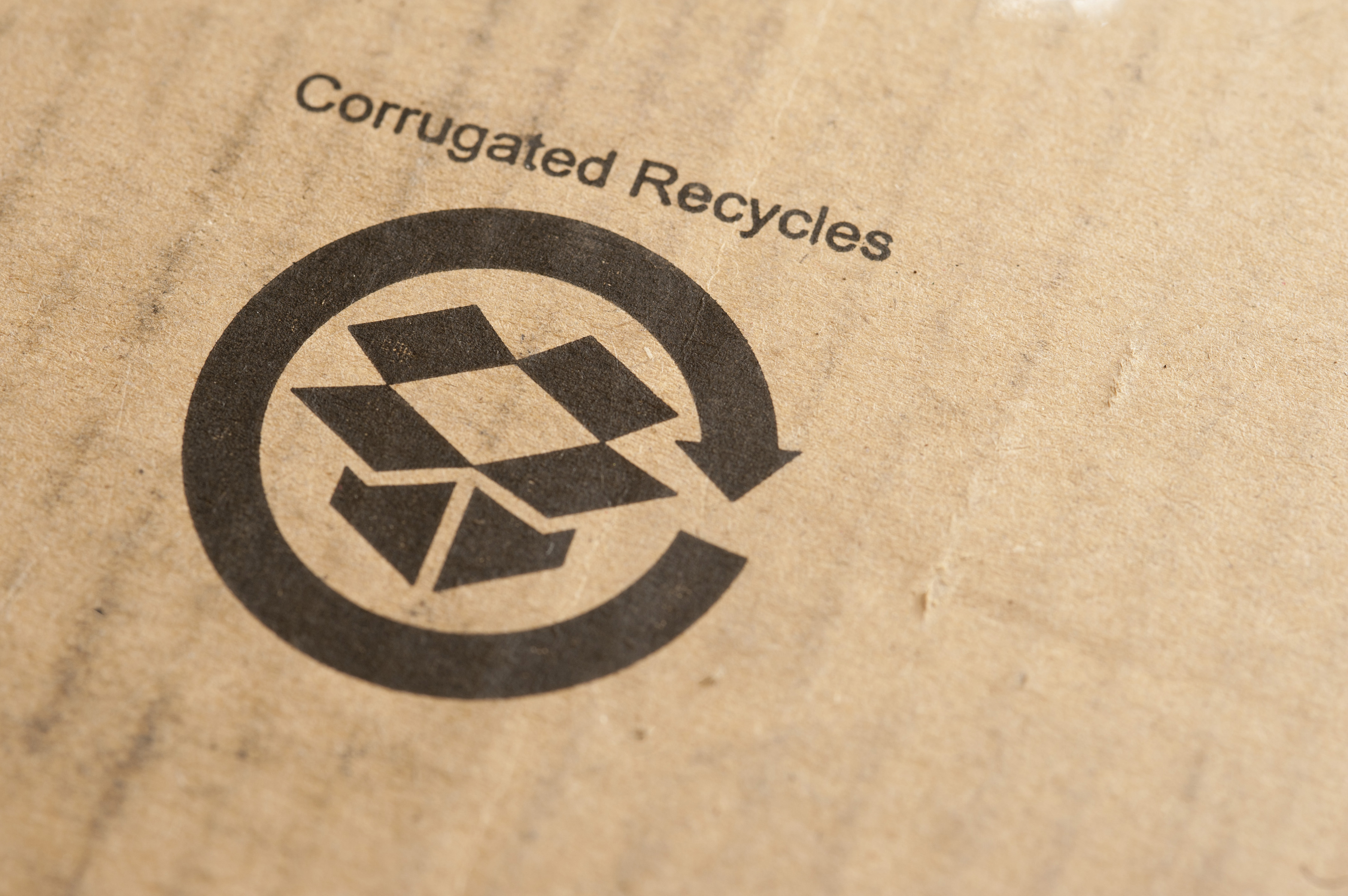 Recycled sign stamped on a cardboard packaging box or carton with the text - Corrugated Recycles - in an environmental concept