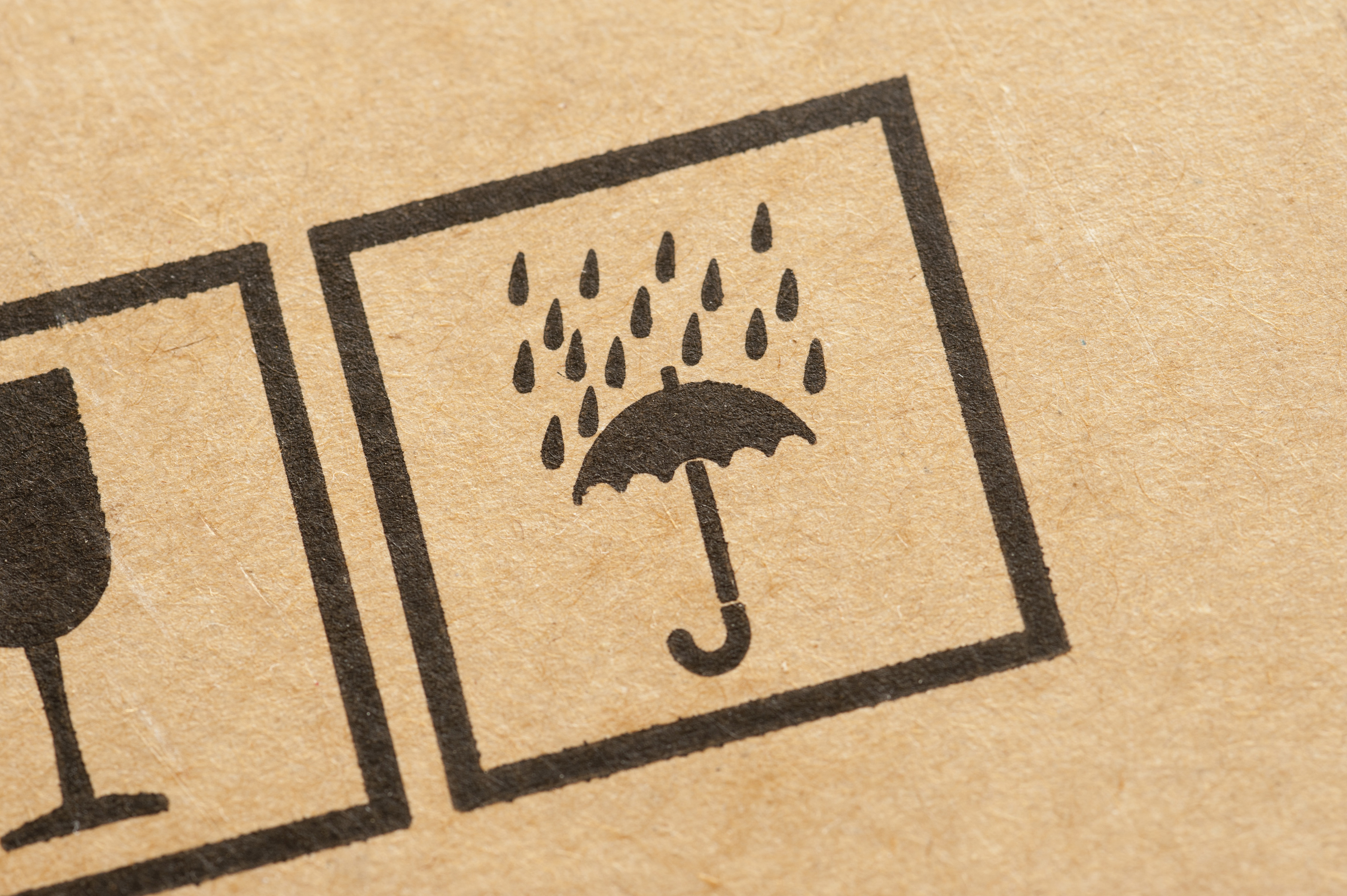 Do Not Get Wet icon stamped on a box used for packaging, removals or storage with an umbrella and raindrops in a close up view
