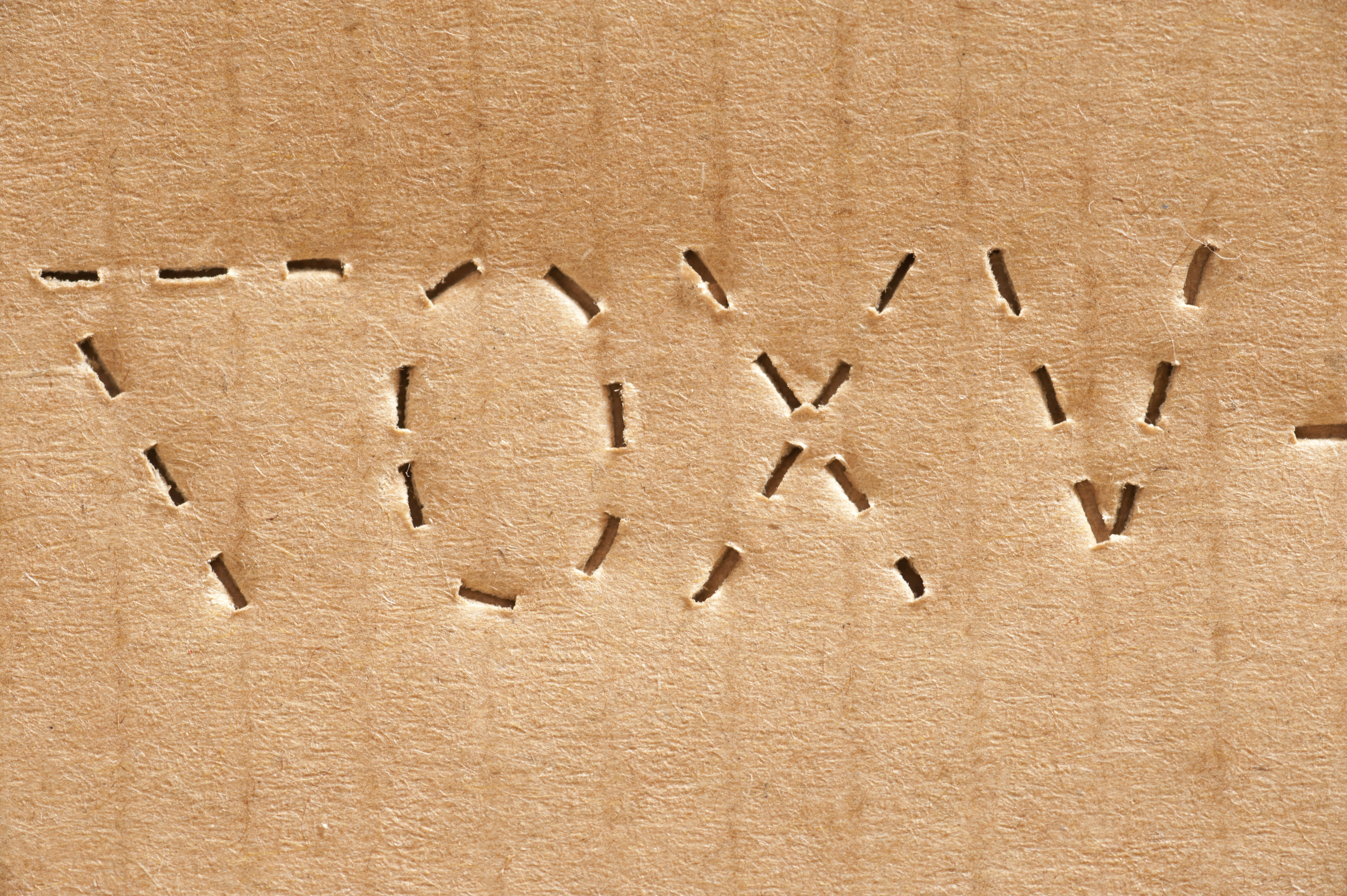 Cardboard stamping on a carton or box with a perforated code with letters and numbers for identification, close up full frame background