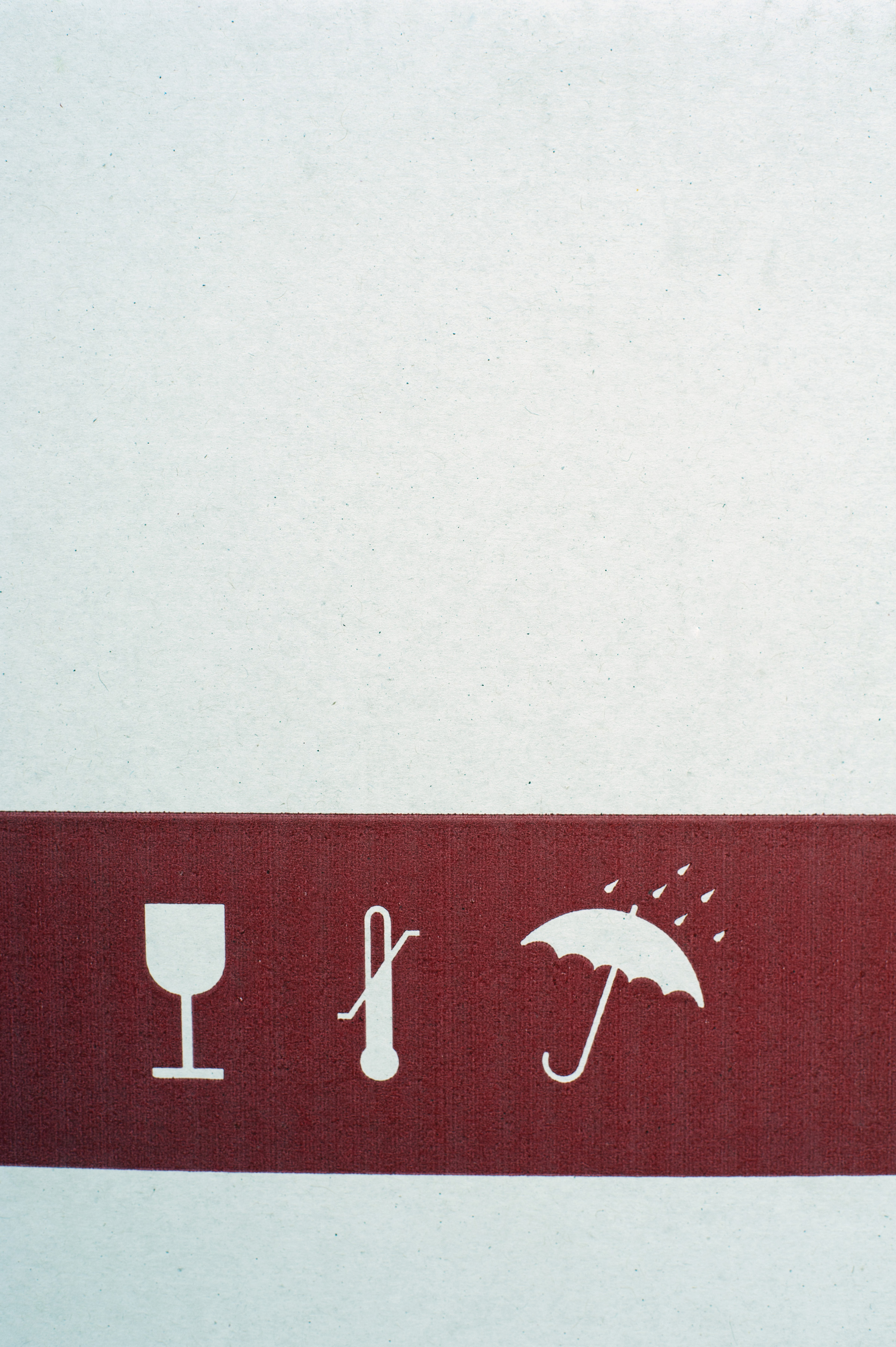 Symbols on the side of a cardboard box with a glass, thermometer and umbrella showing that the contents are fragile and must be protected from rain