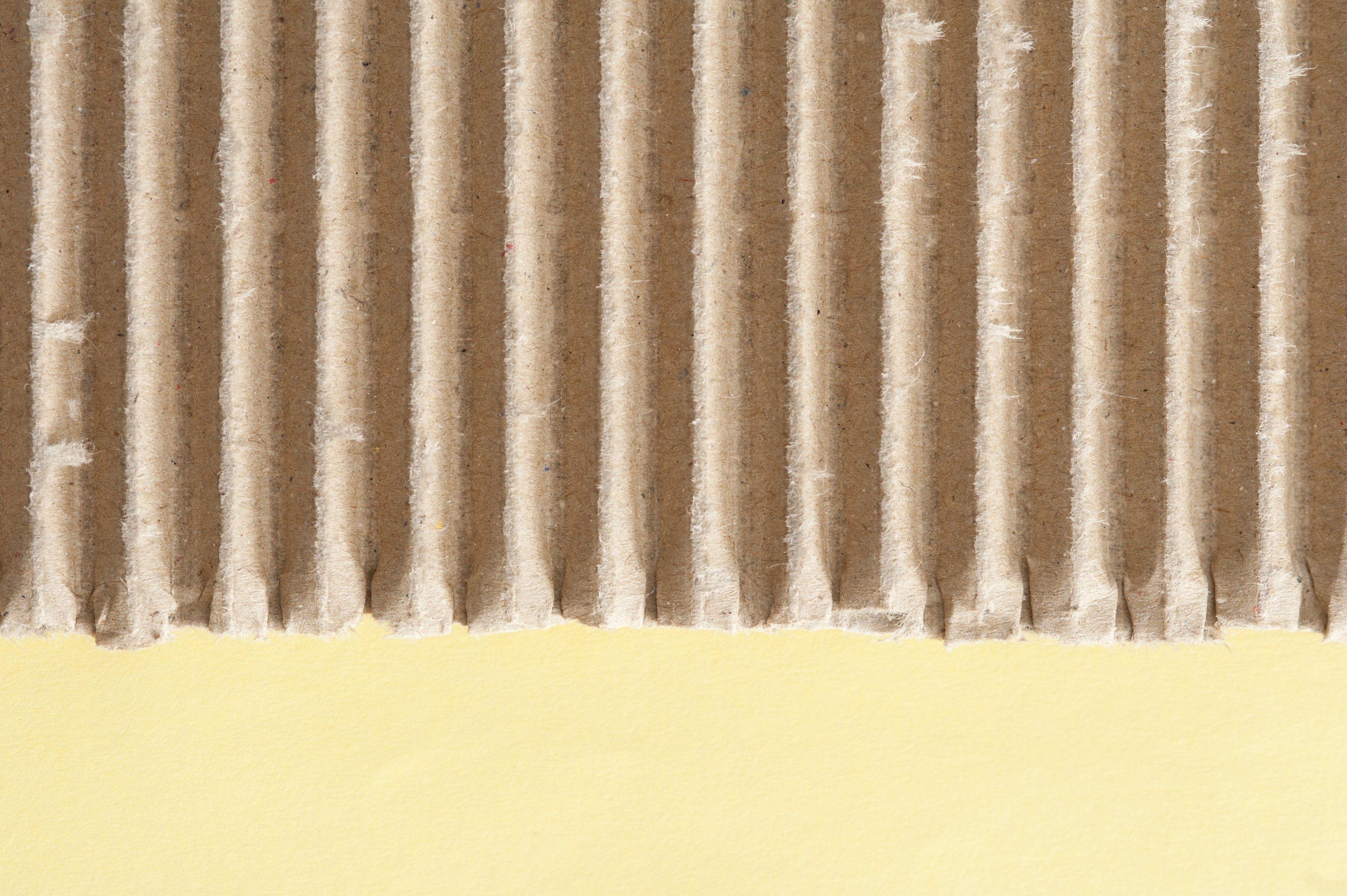 Corrugated brown cardboard texture with yellow copy space below in a close up detailed view from above of paper packaging