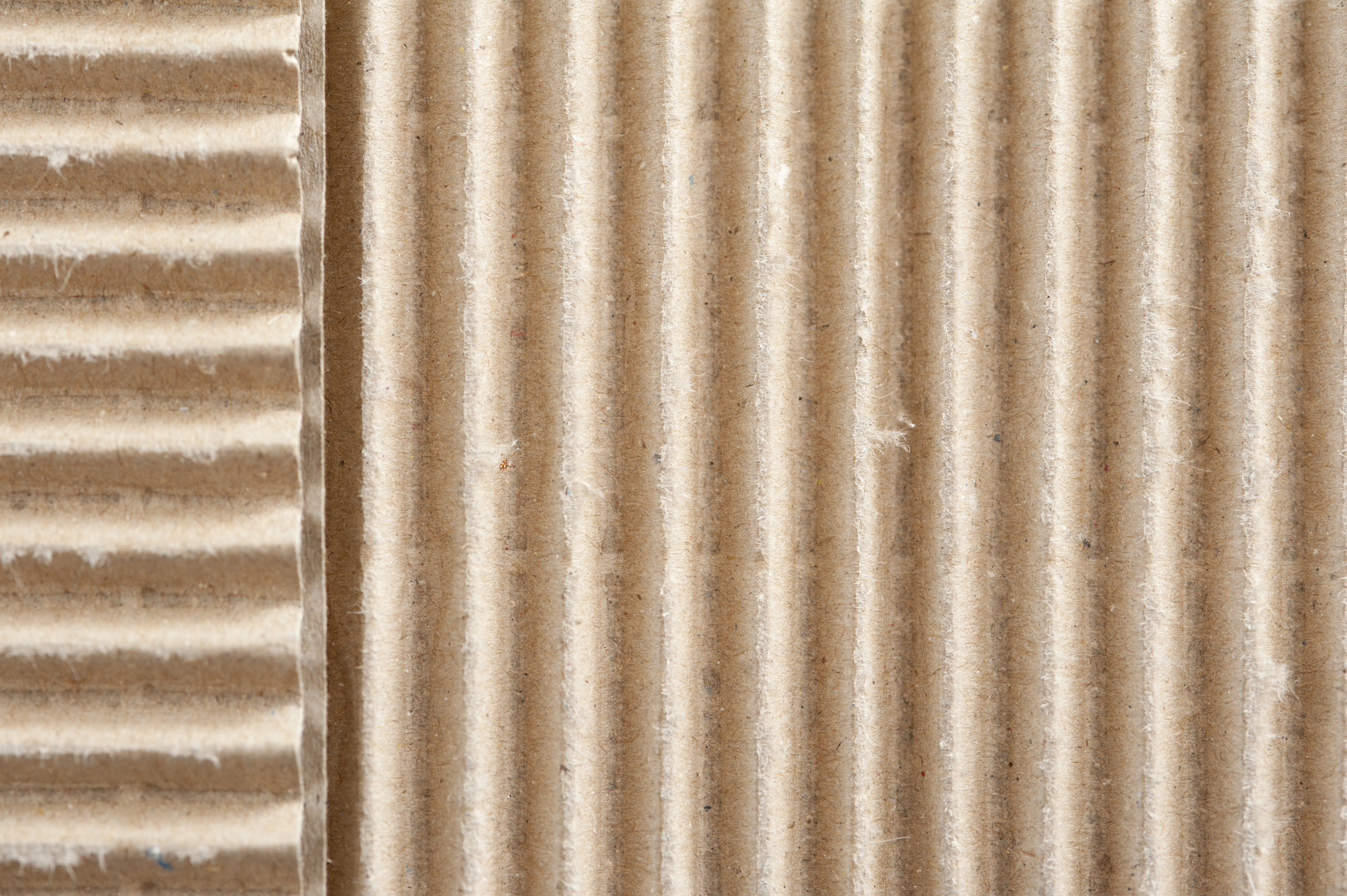 Two corrugated surfaces of brown paper packaging material set at right angles to each other in an overhead full frame background texture view