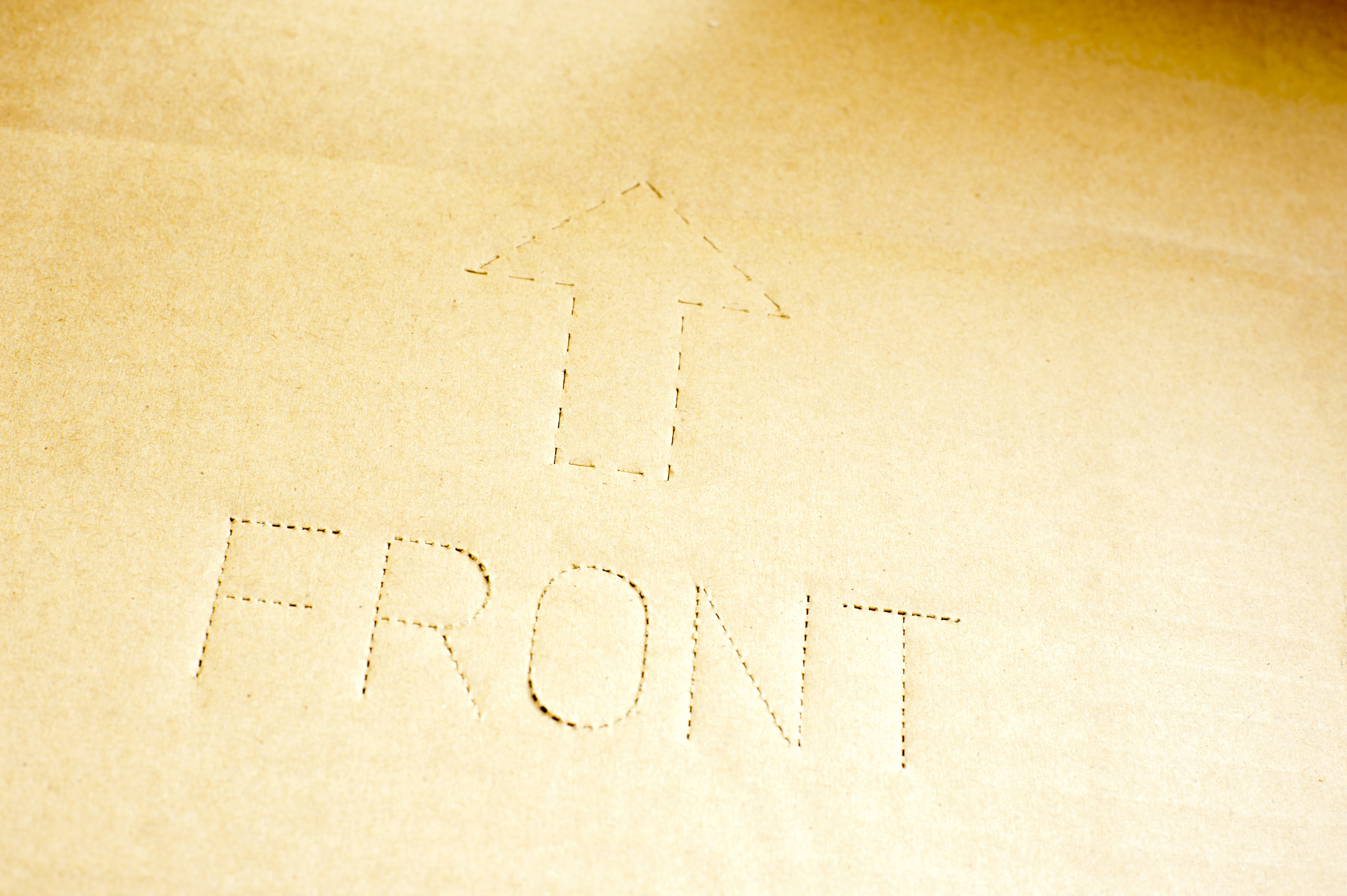 The word front with up arrow on corrugated cardboard as a background with copy space
