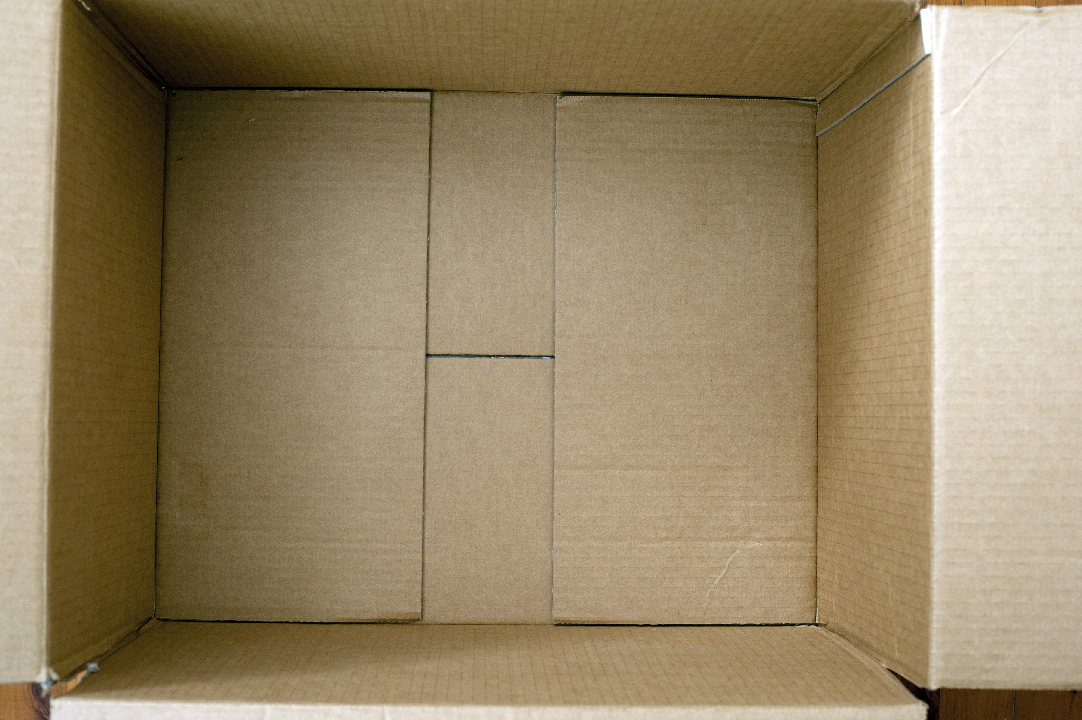 Inside an empty brown cardboard box for packing with an overhead close up view looking down inside the open flaps