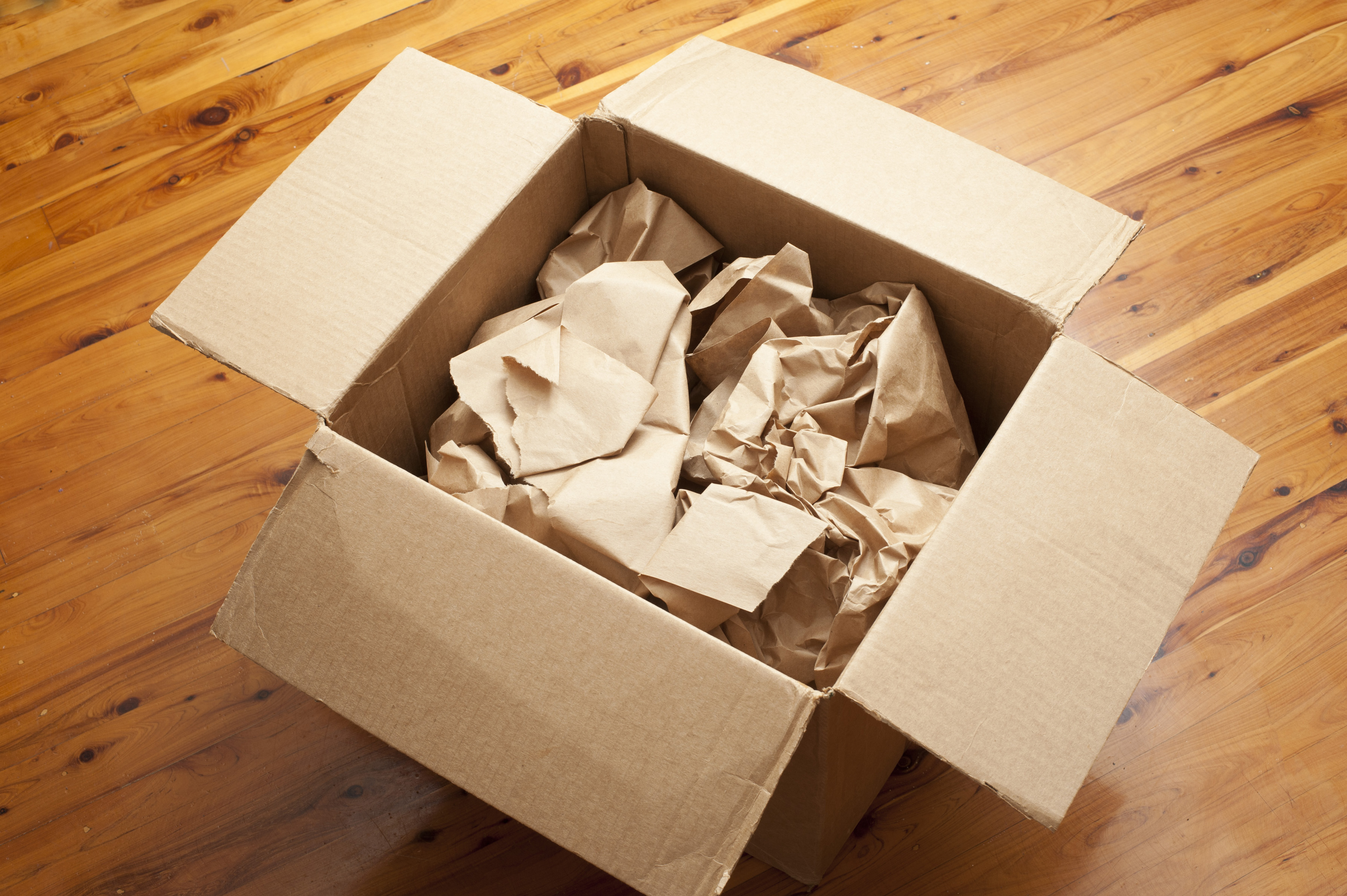 Open brown cardboard packing box with crumpled brown paper for packaging inside on a wooden floor, high angle view