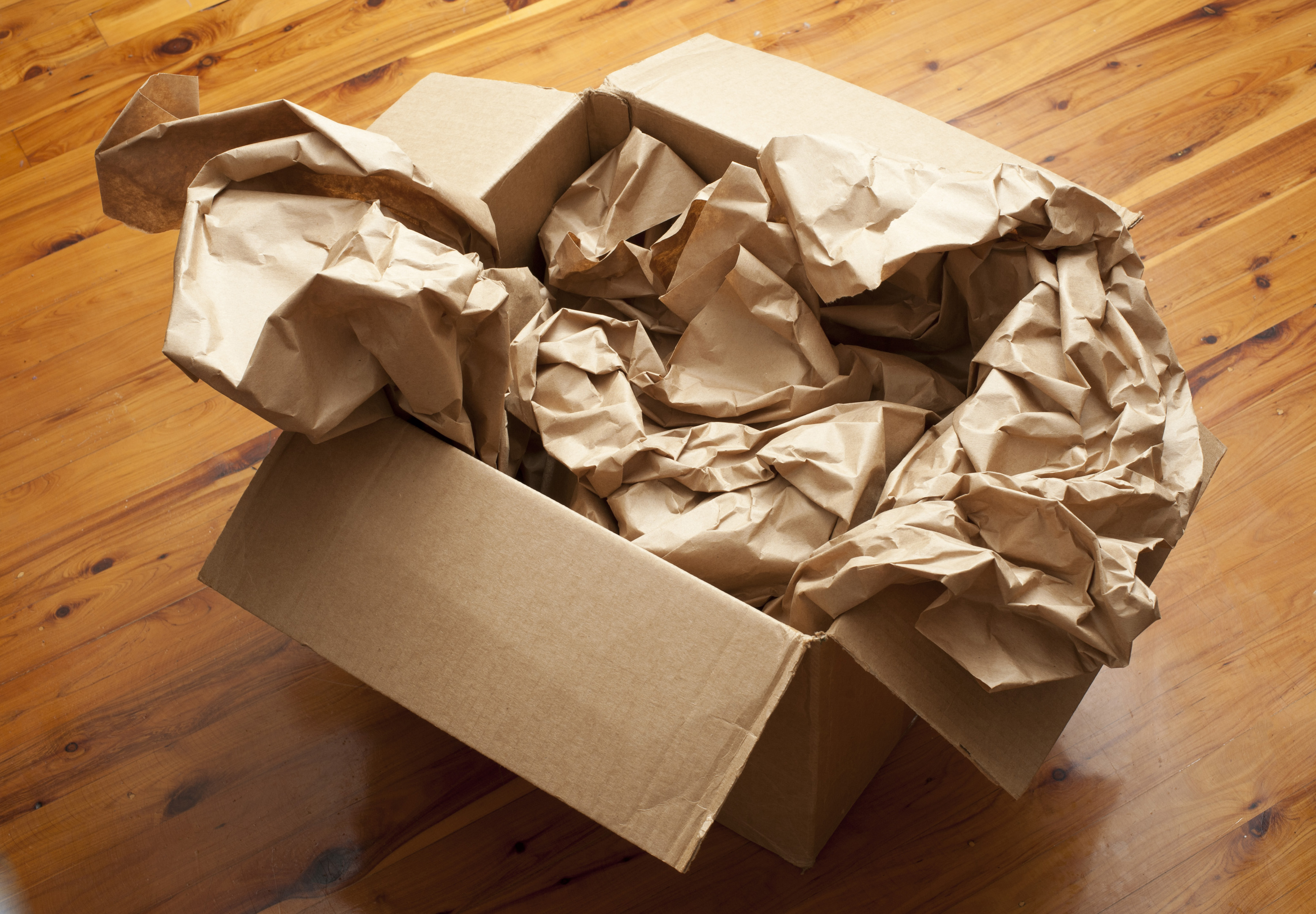 Open brown cardboard box with crumpled brown paper inside for packaging and storage viewed high angle on a wooden floor