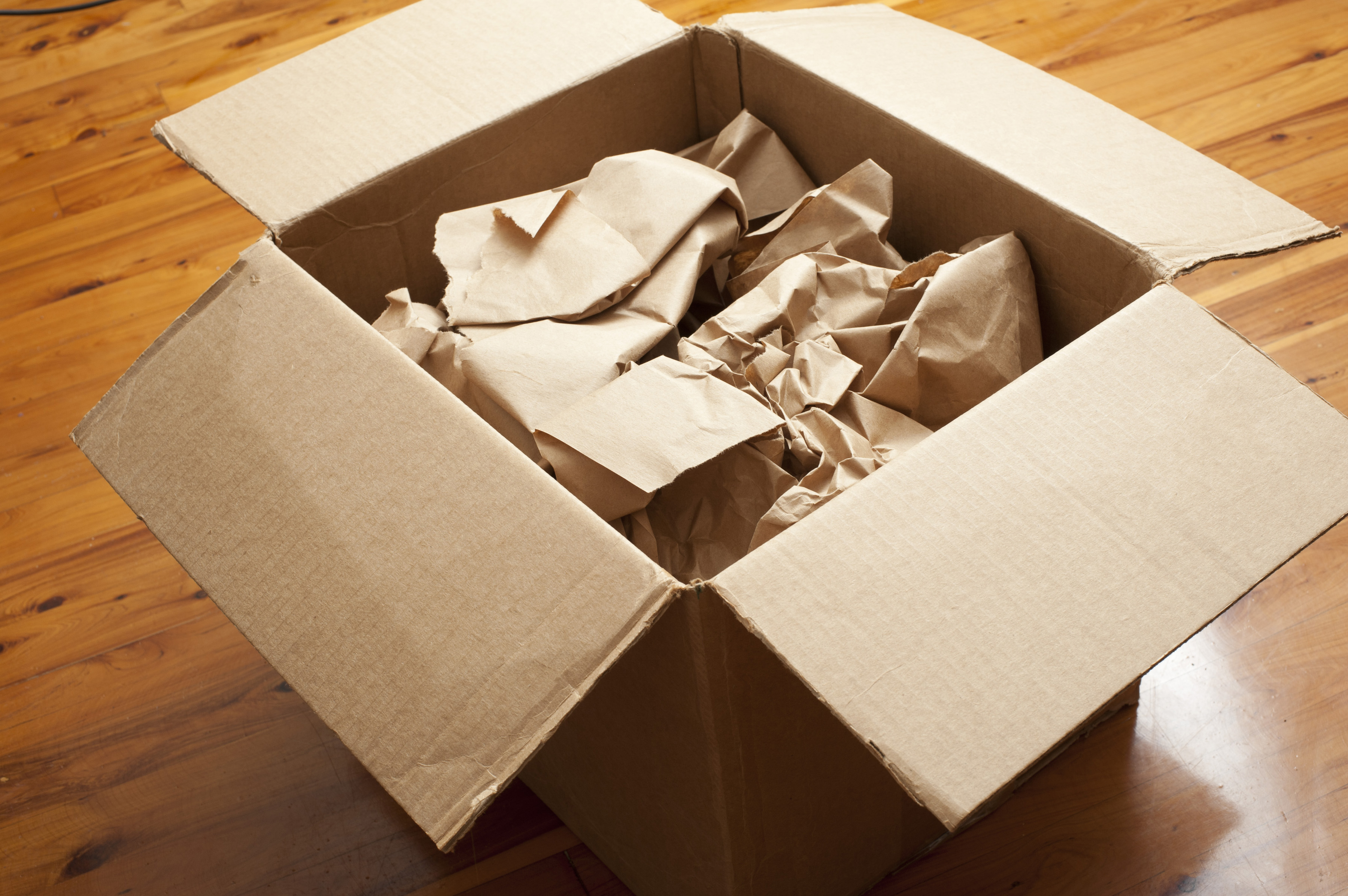 Open brown cardboard box or carton with crumpled brown paper for packaging inside on a wooden floor