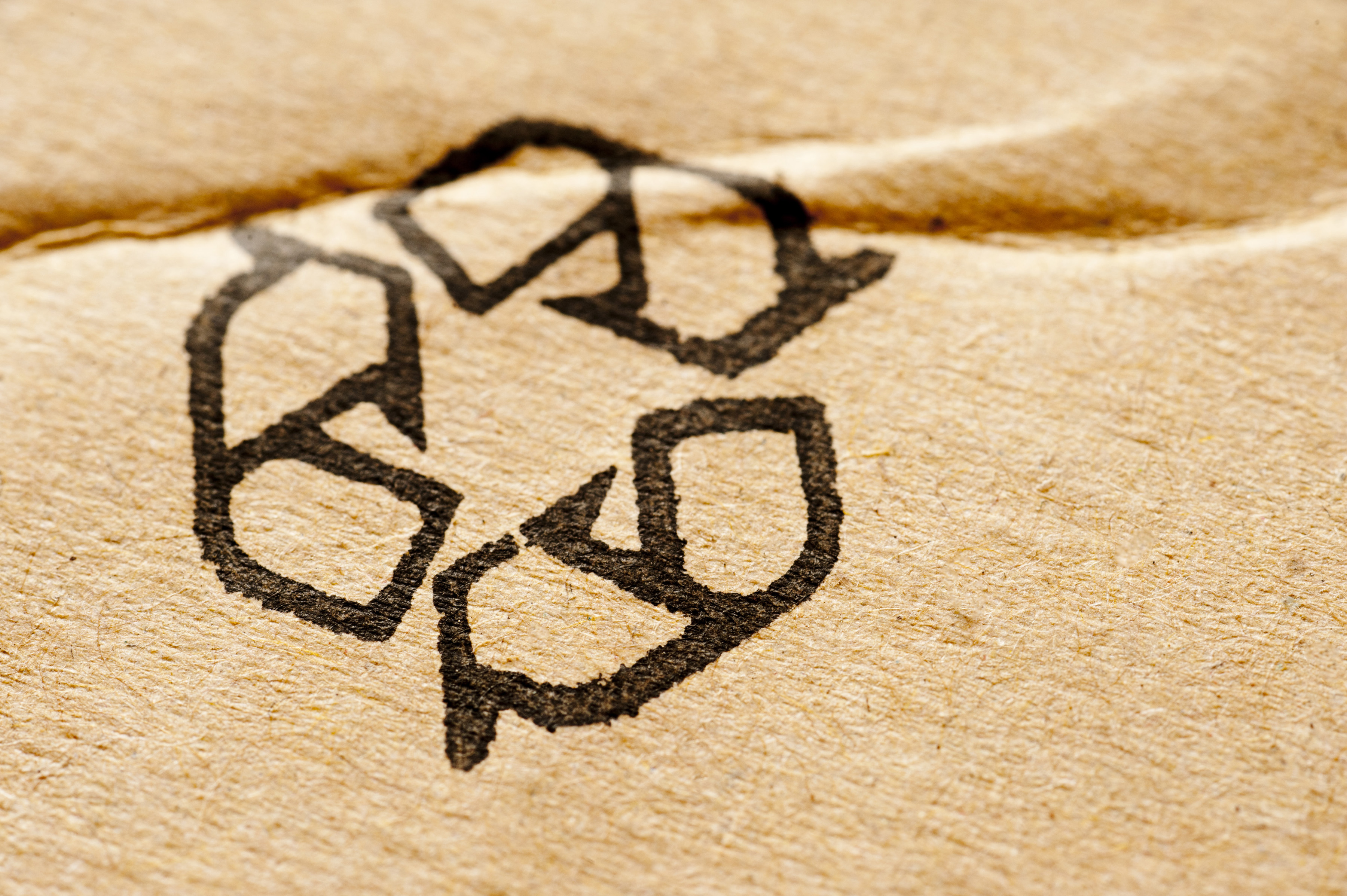 Recycle symbol on a cardboard background texture on commercial packaging with copy space alongside
