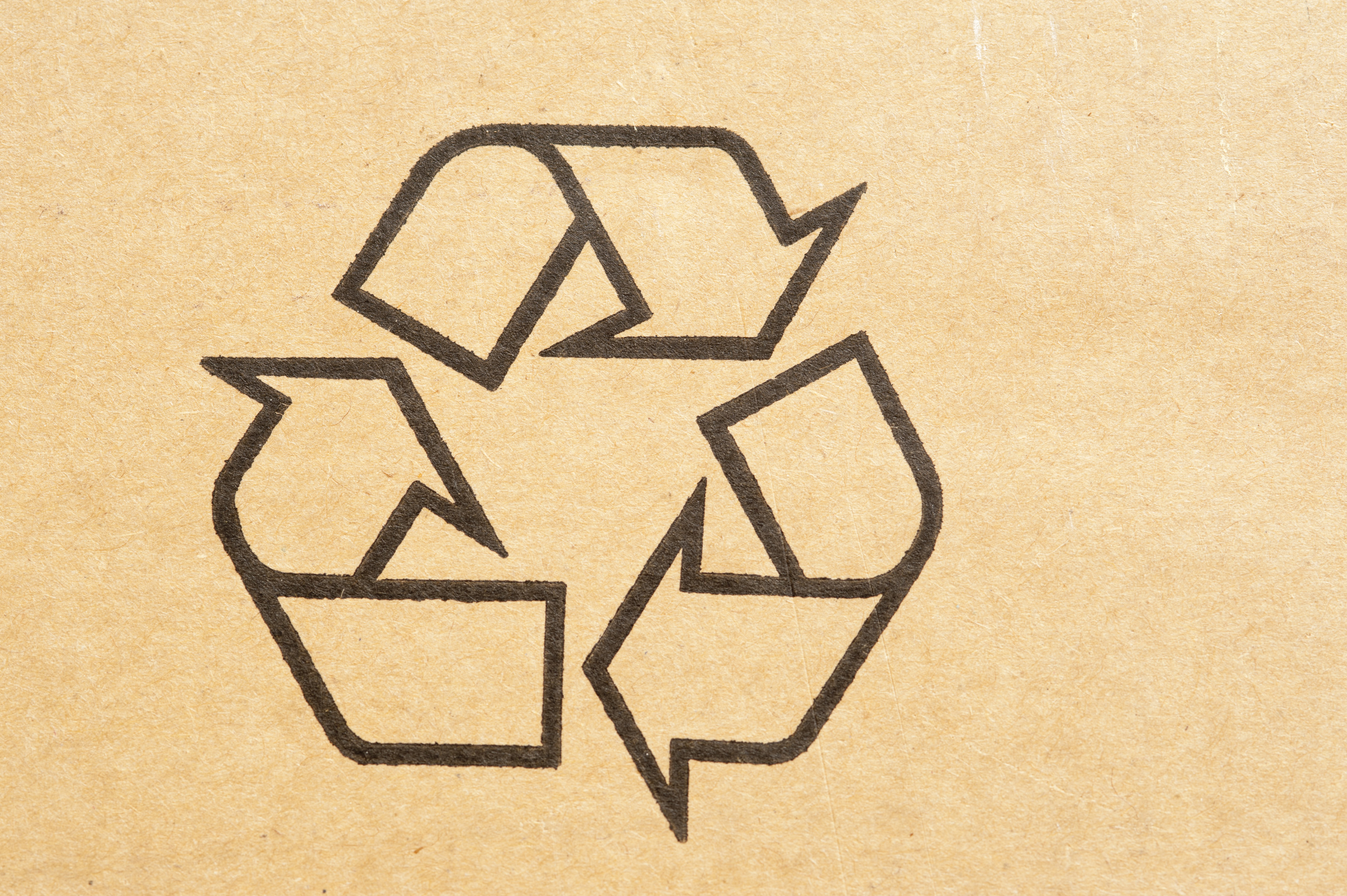 Recycle symbol stamped on a brown cardboard carton to be recycled and reused to save the environment from pollution