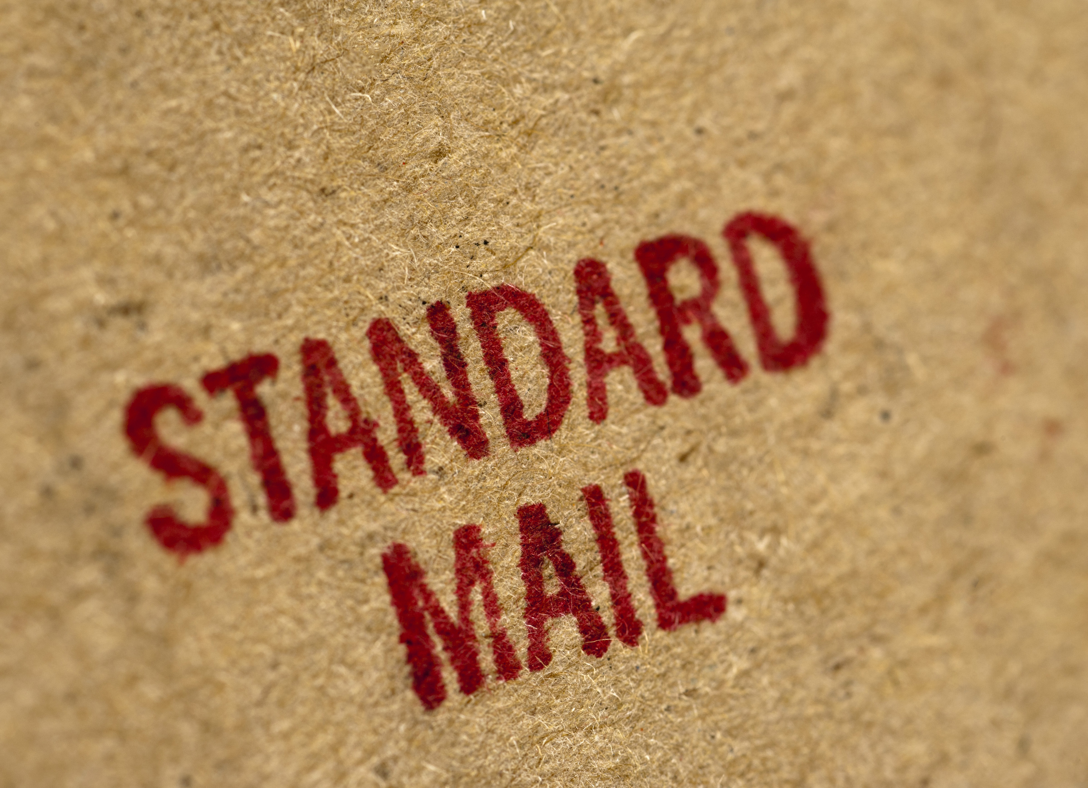 Standard Mail postage rate stamped in red on the side of a brown cardboard package , close up full frame texture background