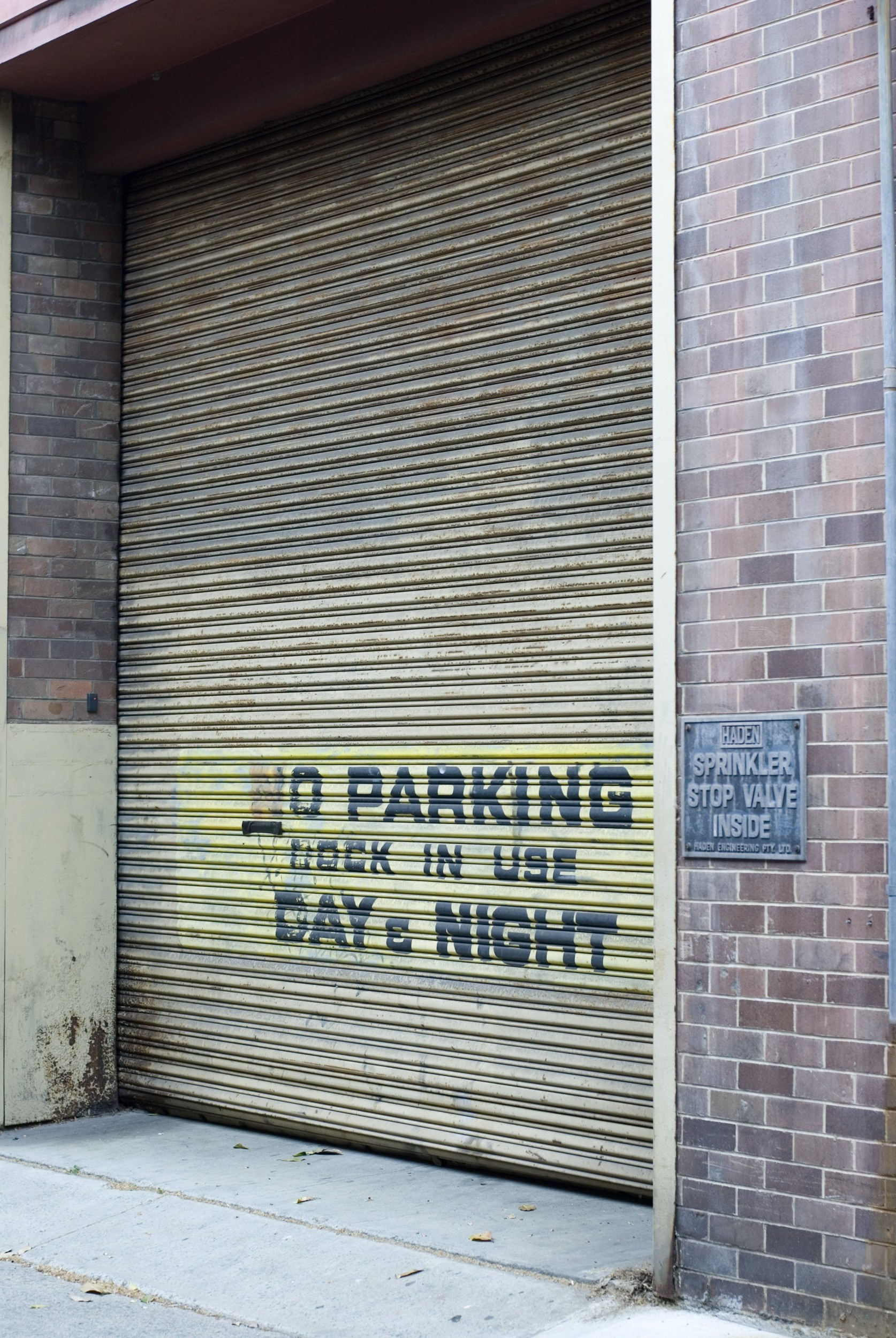 an alleyway roller shutter door marked with no parking