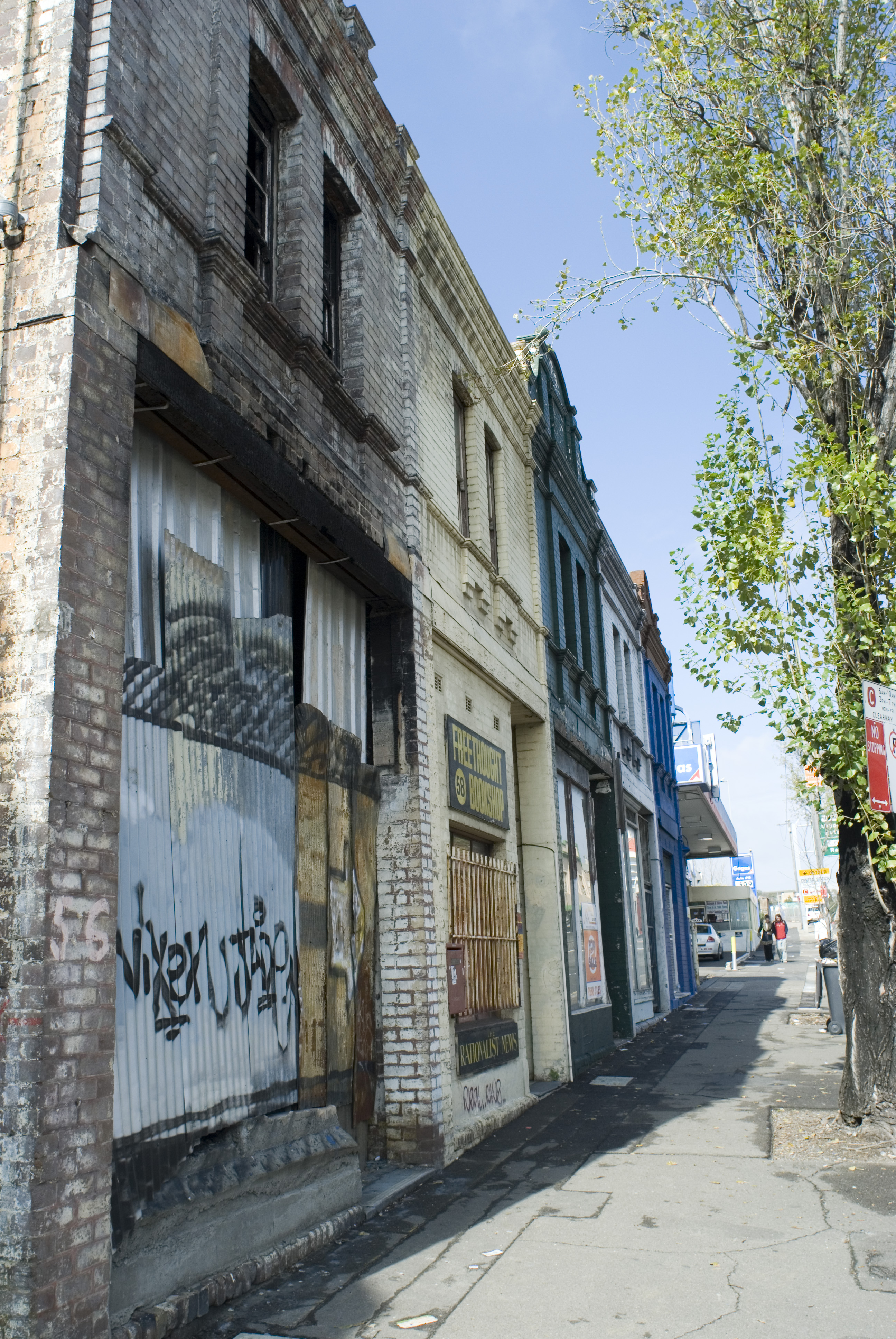 a grungy urban street scene, row of derelict buildings borded up and vandalised