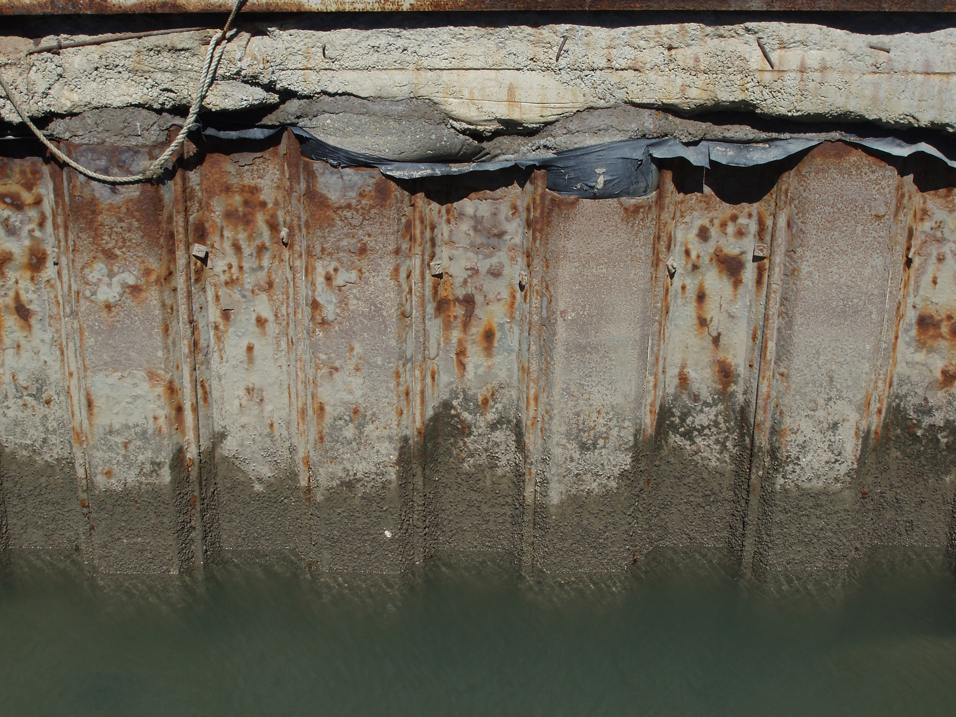 a rusty quayside made from metal pilings