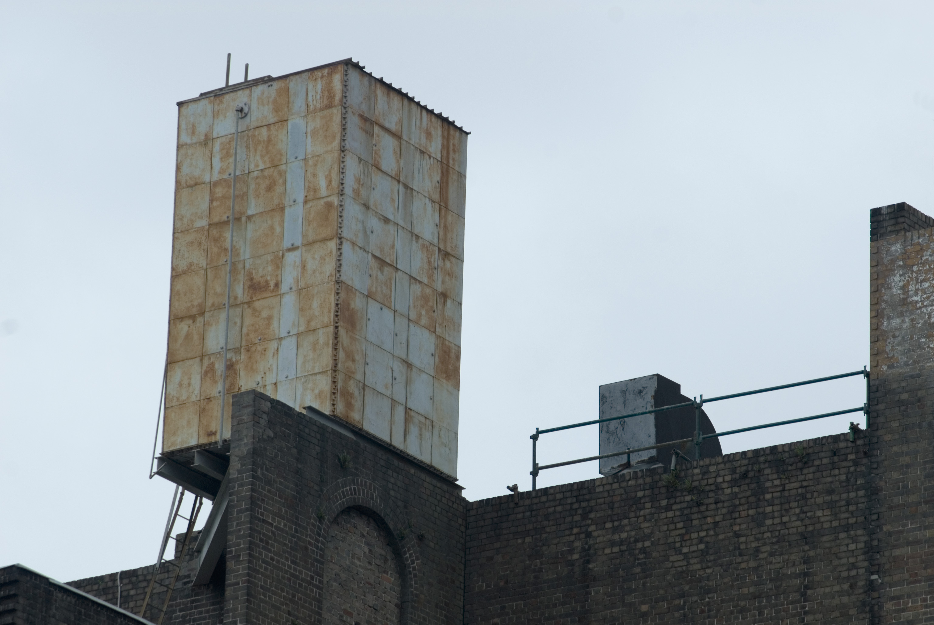 a rusty old rooftop water tank