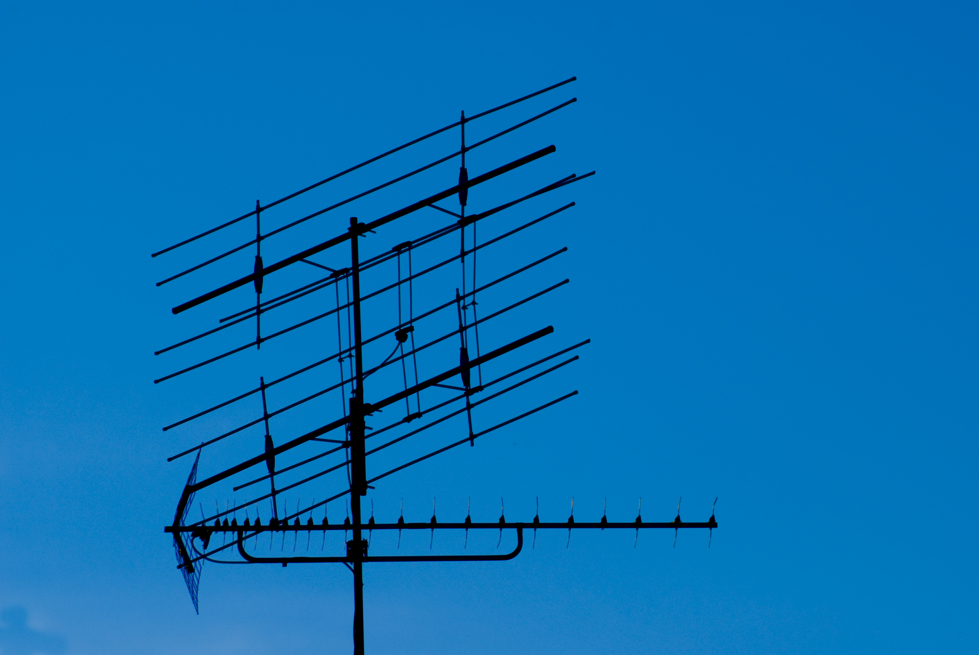 roof top antenna pictured against a deep blue sky