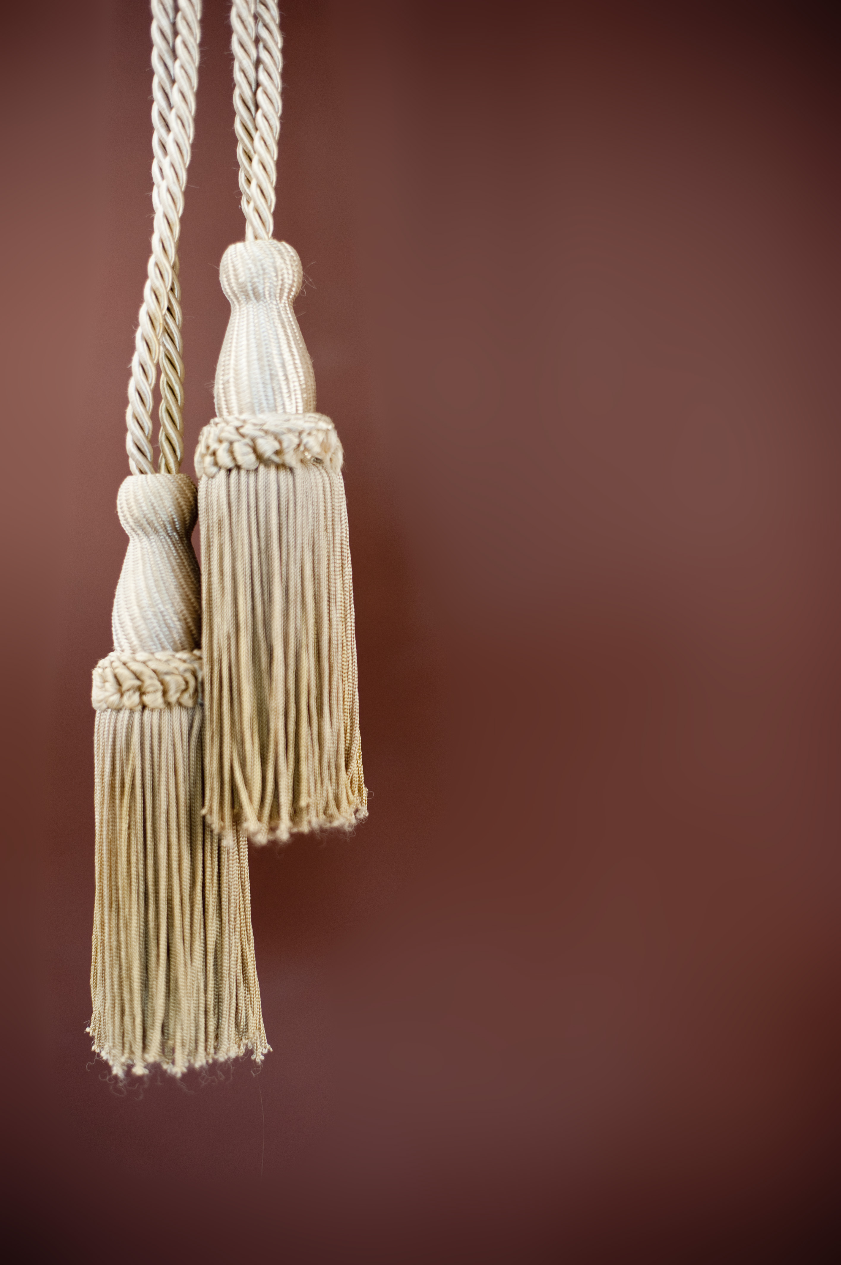 ornate gld coloured curtain tassels on a brown background