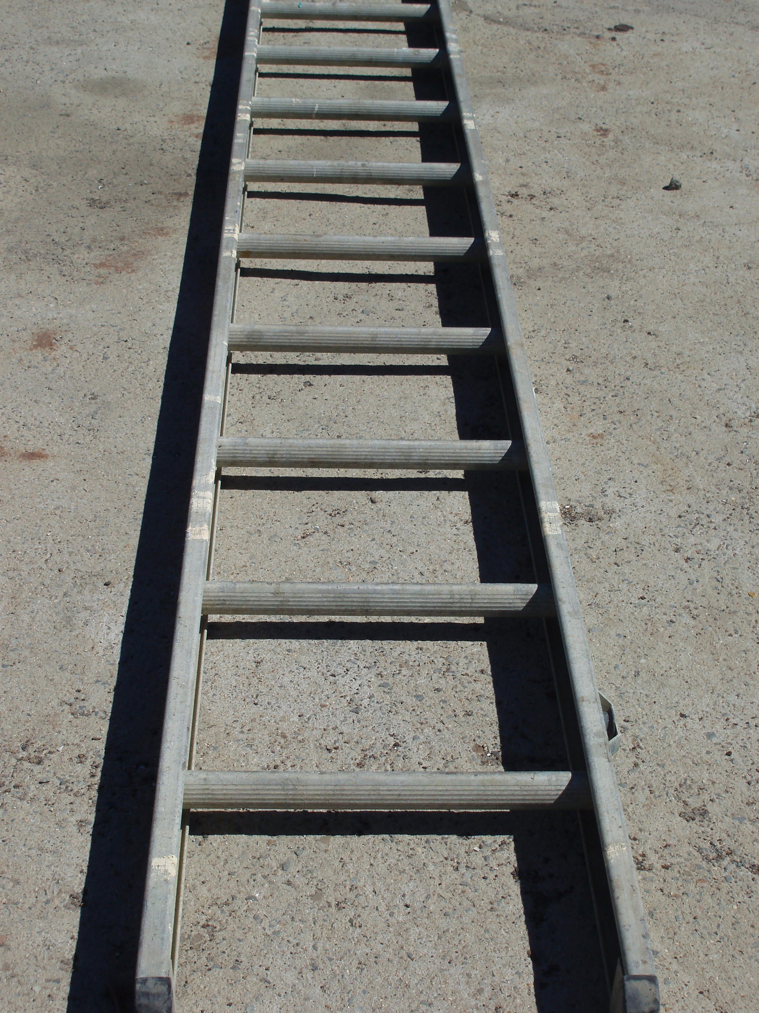 a dirty aluminum ladder laying on the ground