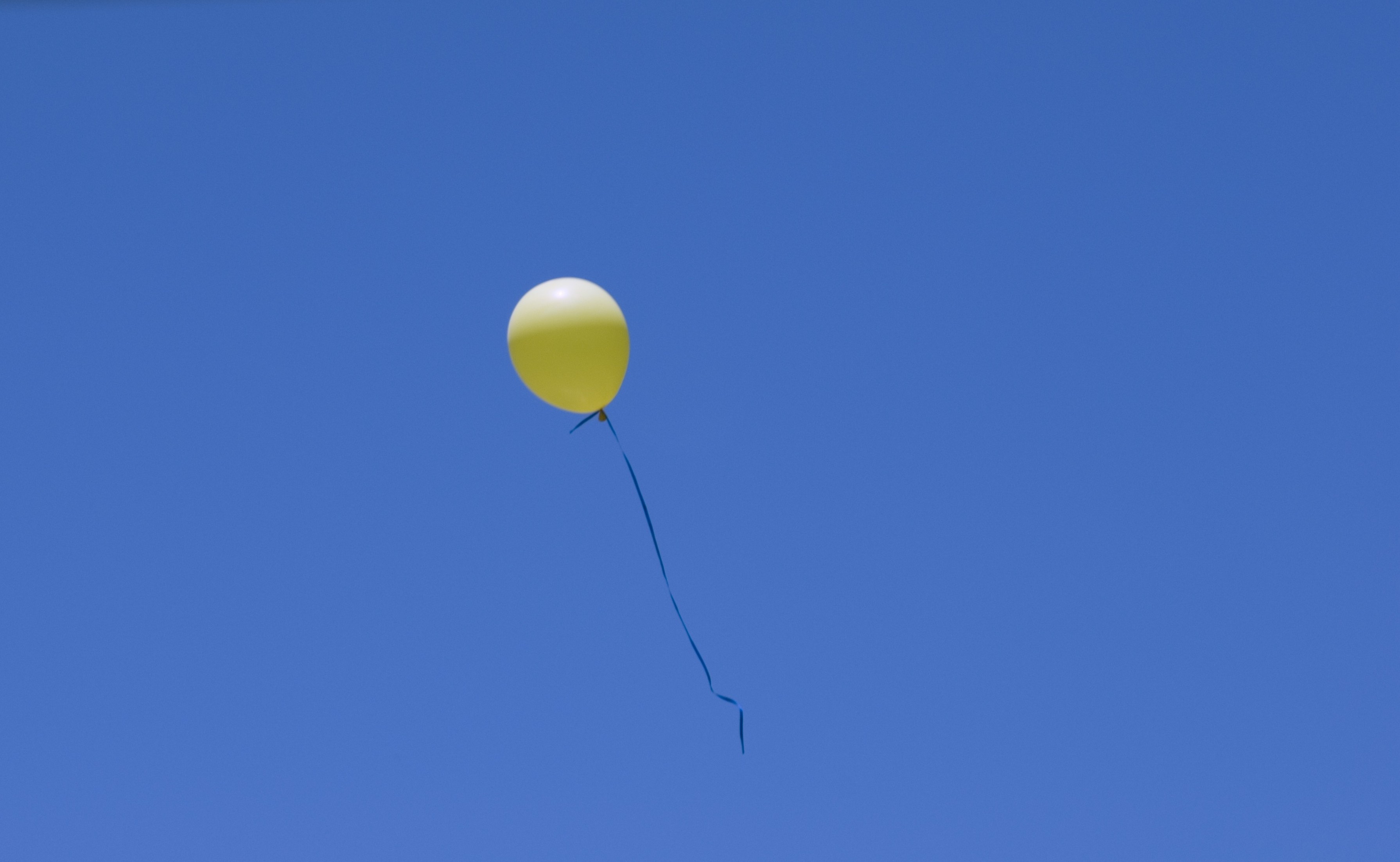 a bright yellow balloon floating in a blue sky