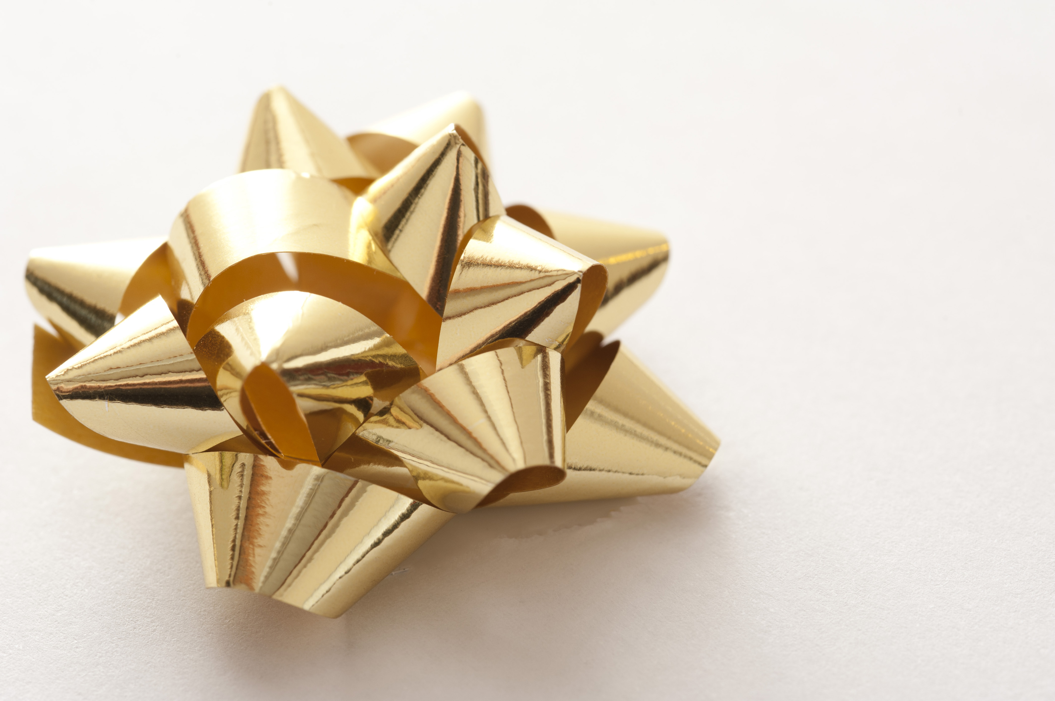 golden shiny gift wrap bow on a white backdrop
