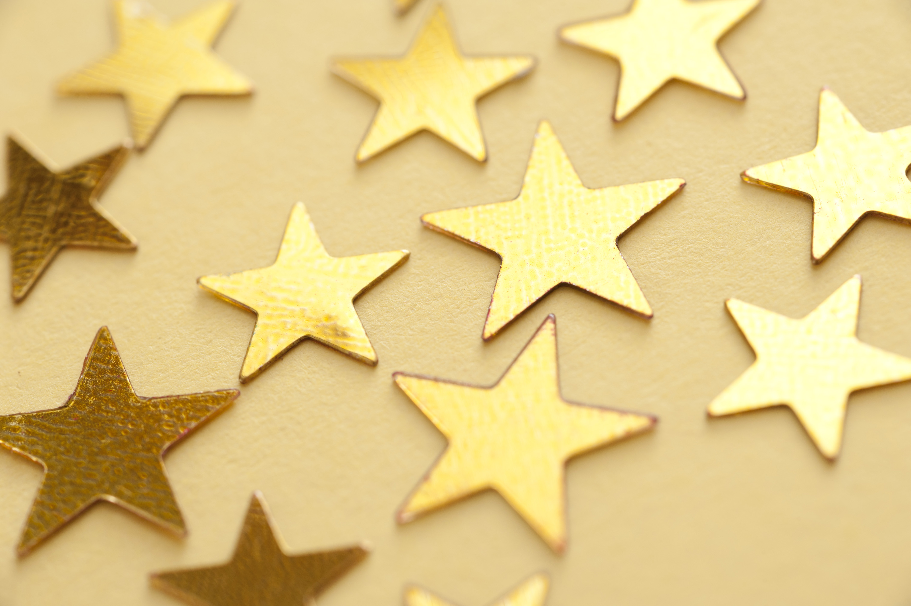 Festive gold stars scattered on a golden yellow background viewed at an oblique angle with focus to the central two stars in a festive or Christmas background