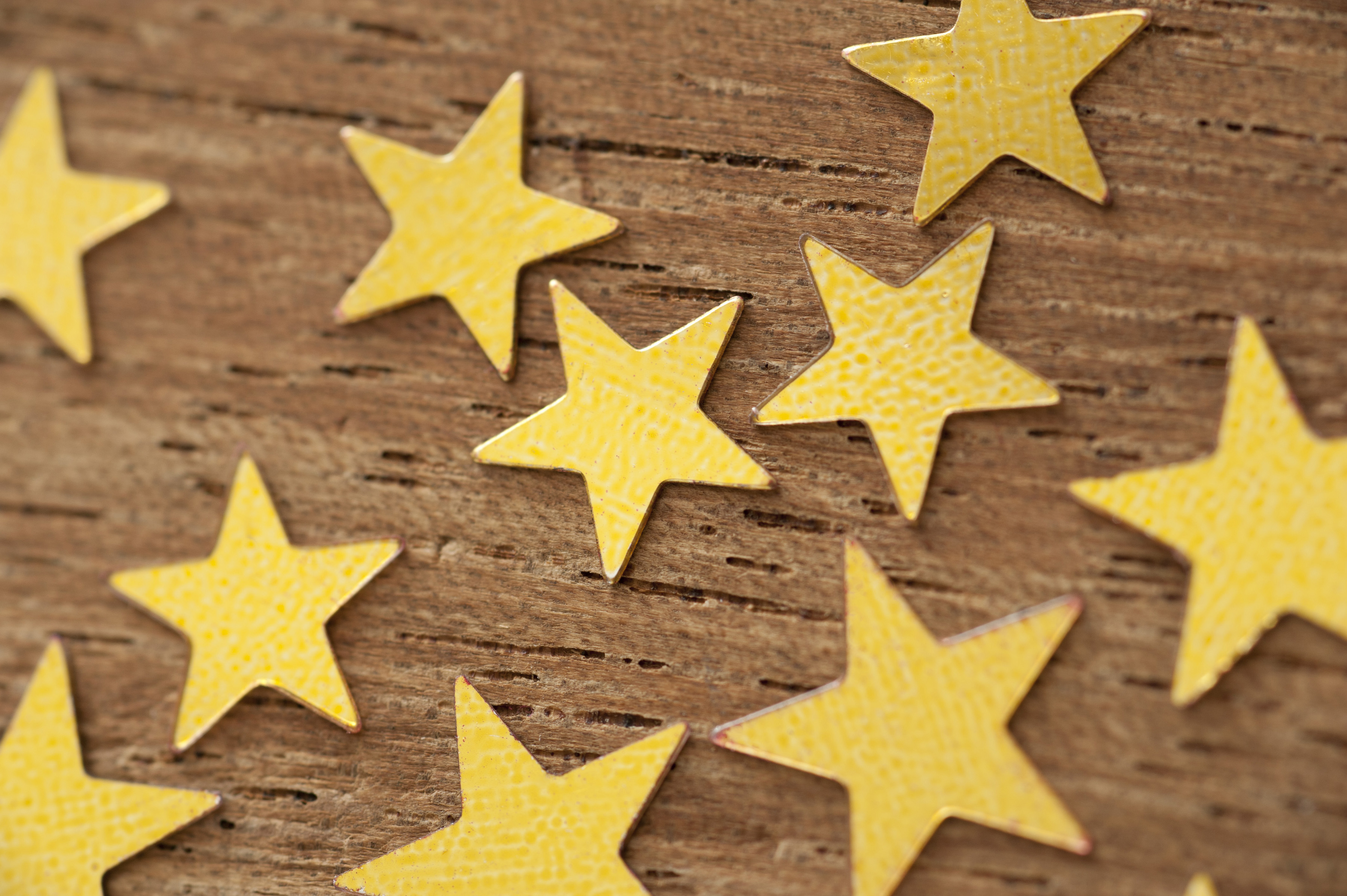 Concept Background Image of Golden Stars in Various Sizes Scattered on Wooden Background