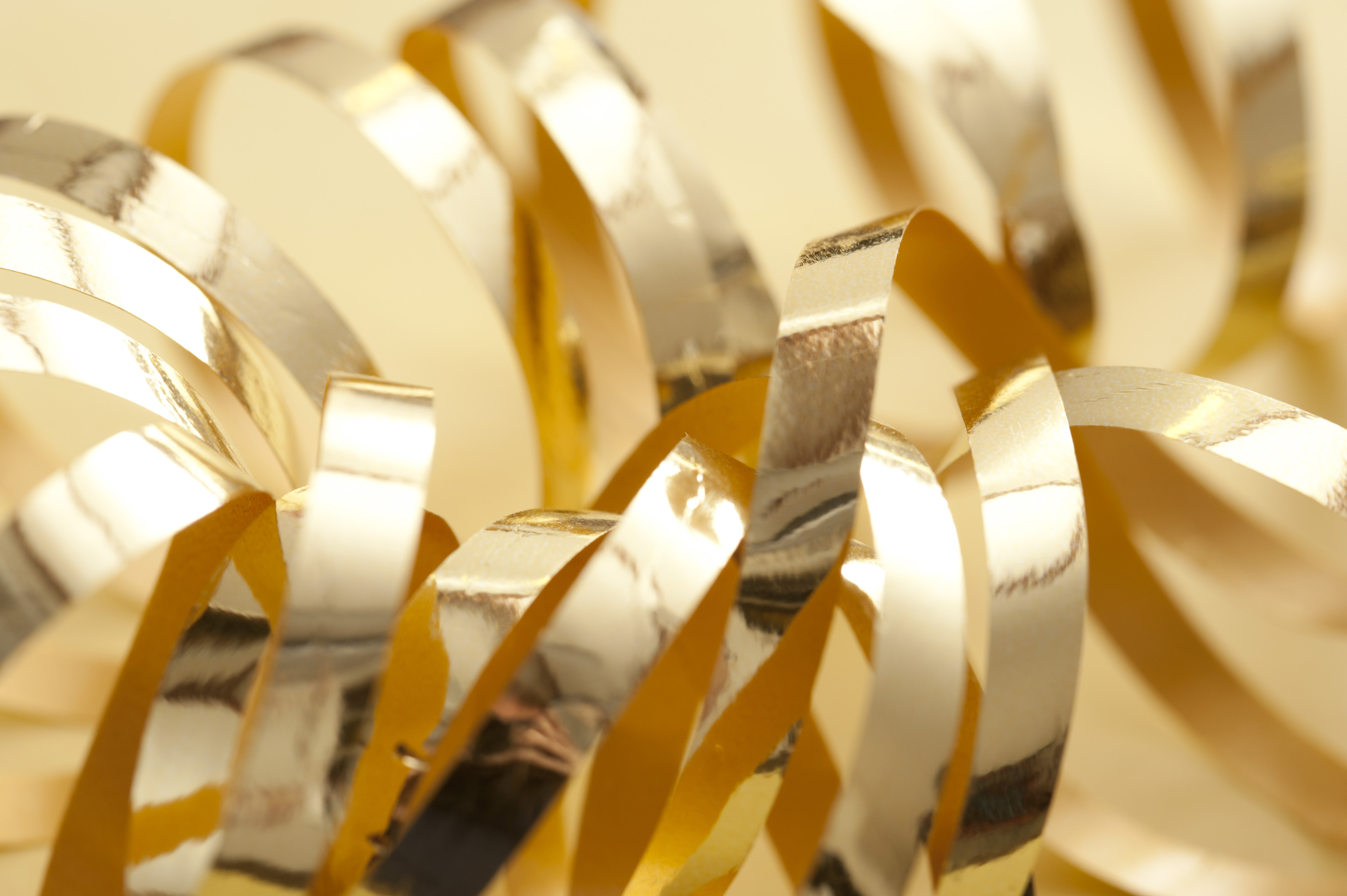 Close up of coiled metallic gold ribbons for a festive celebration on a yellow background, suitable as a Christmas theme