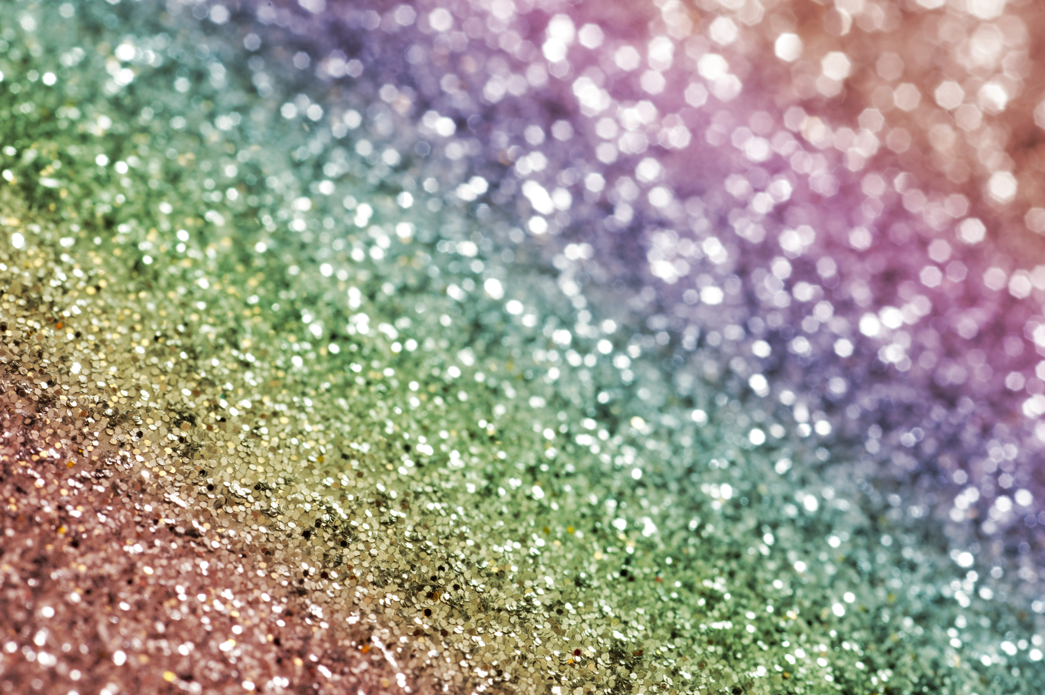 Rainbow colored glitter background in the colors of the spectrum arranged in a diagonal line for holiday or festive themed concepts