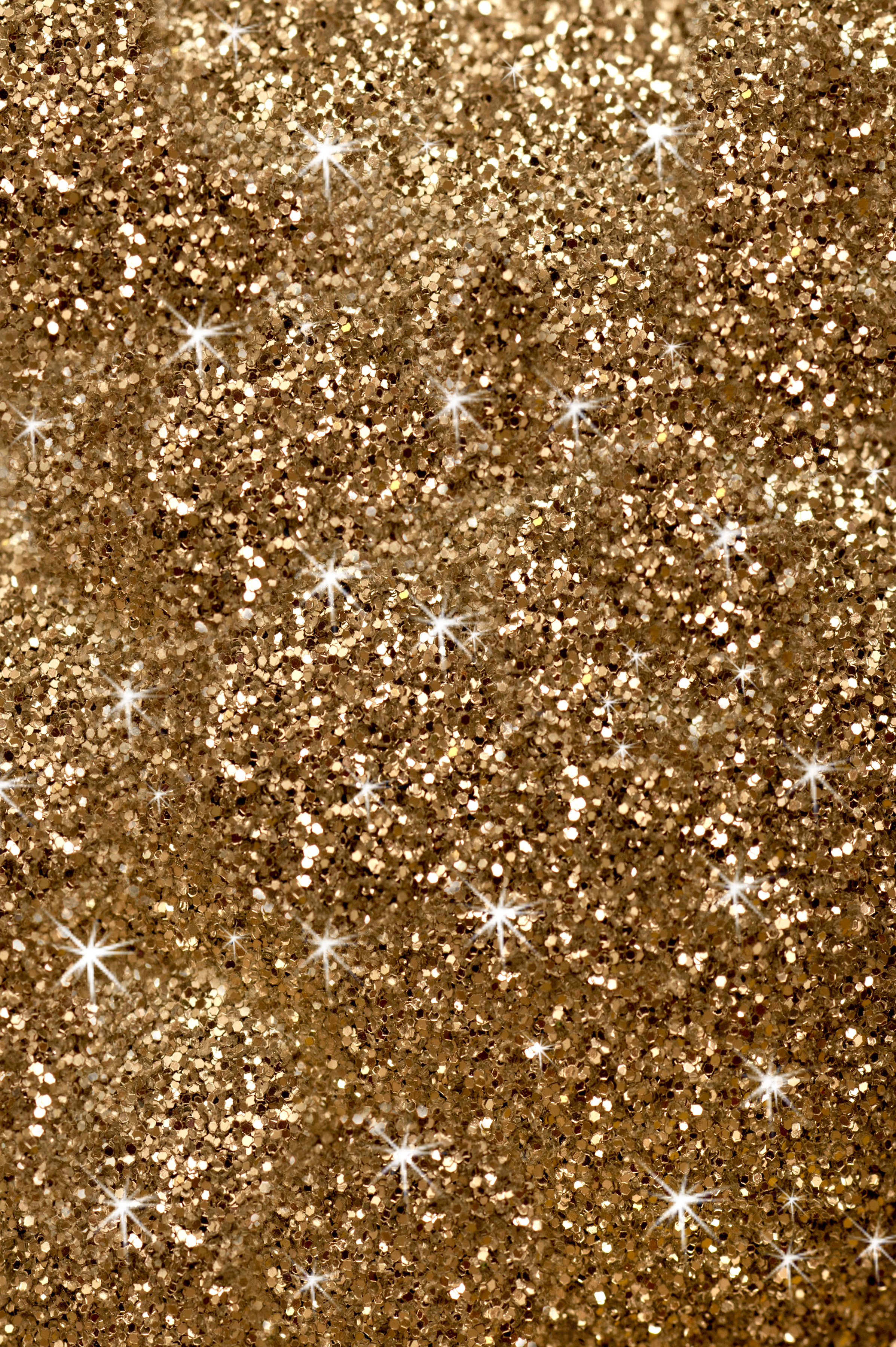 Twinkling sparkling gold glitter texture in a full frame background for your Christmas, carnival, holiday or festive themed greeting