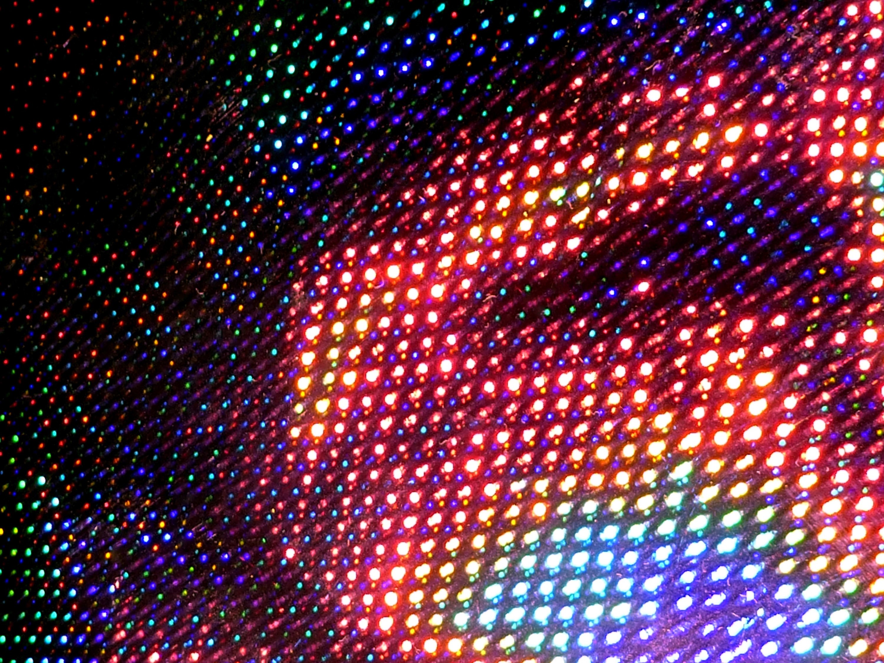 colourful pixels of light illuminated on a dark backdrop with noise and grain