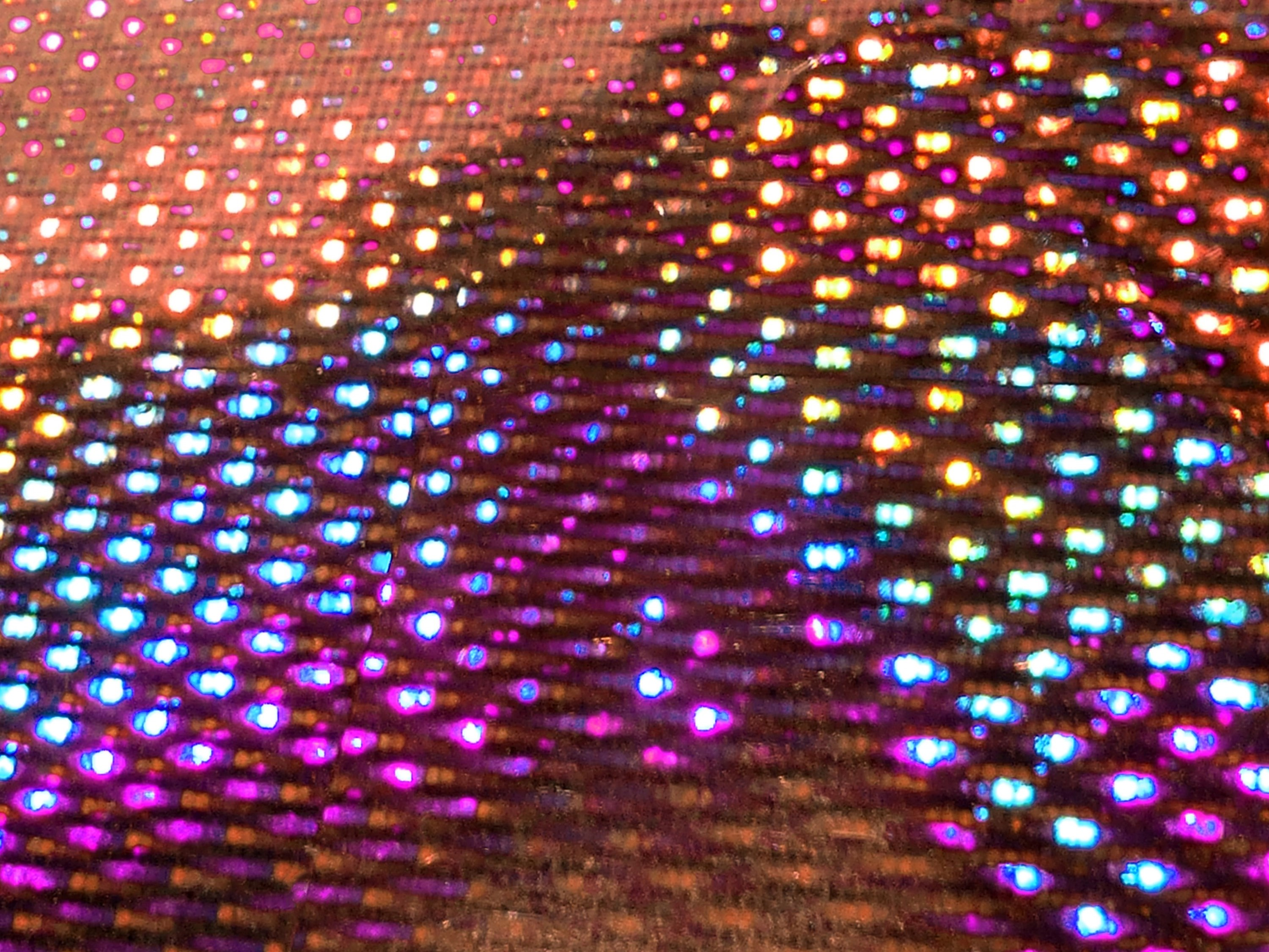 angled image of a sheet of holographic material with lots of colorful points of light