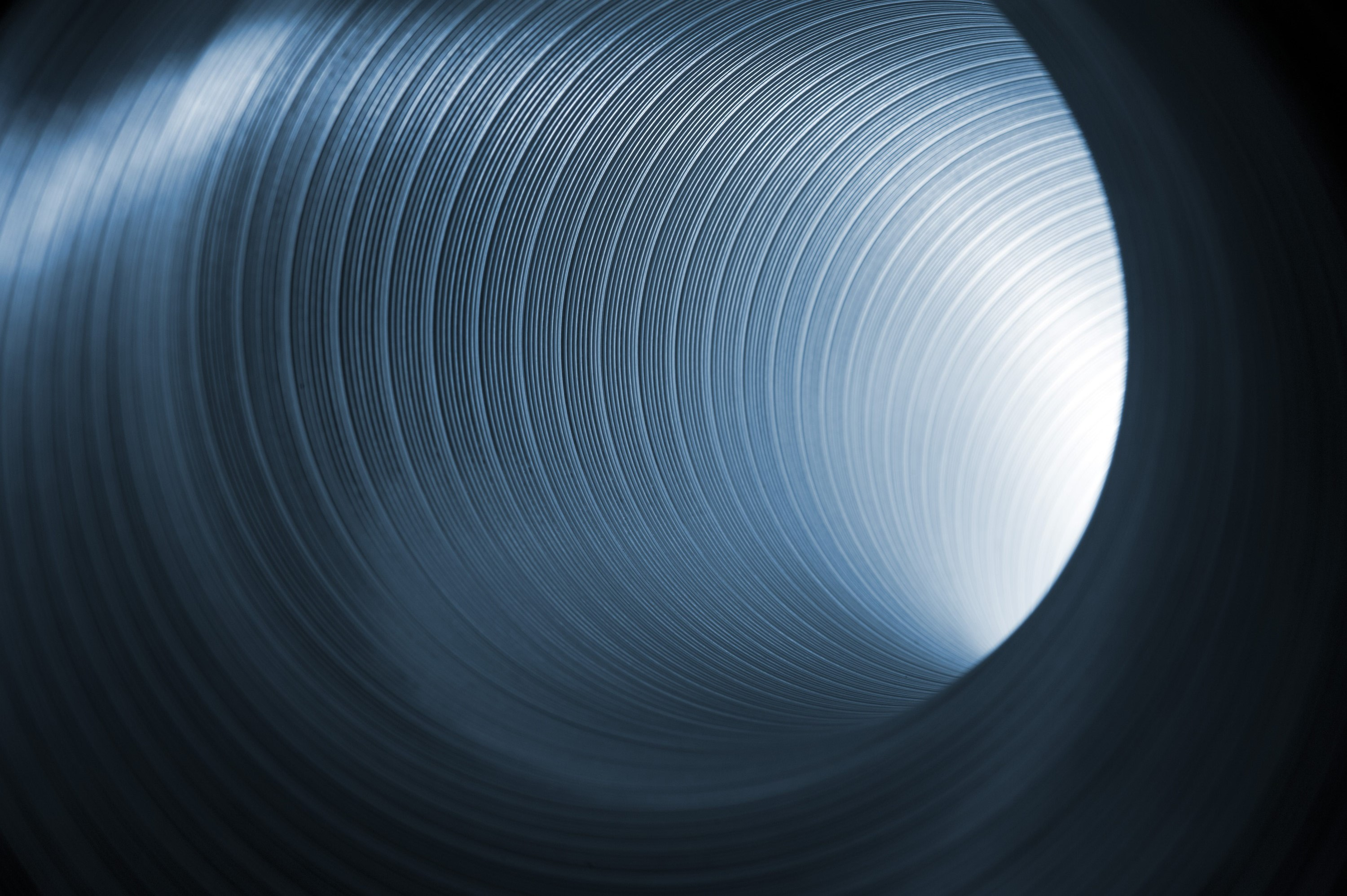 abstract image of light glowing at the end of a metal tube
