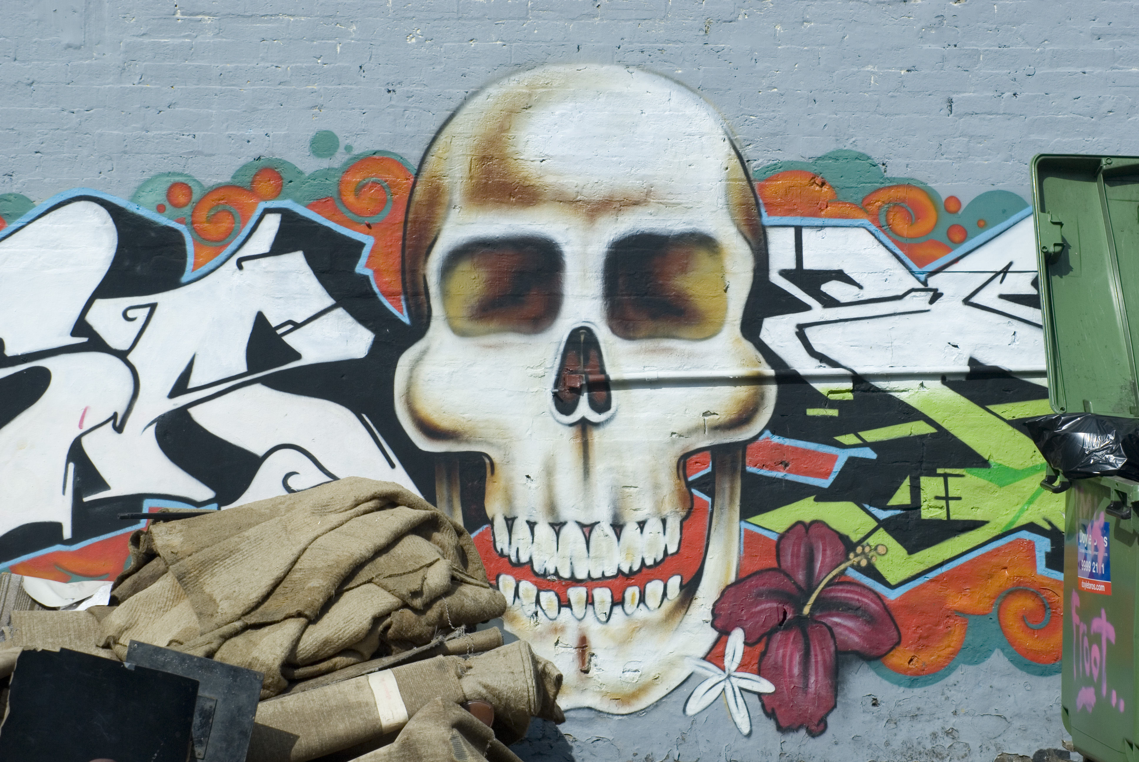 a wall covered in graffiti with a skull motif