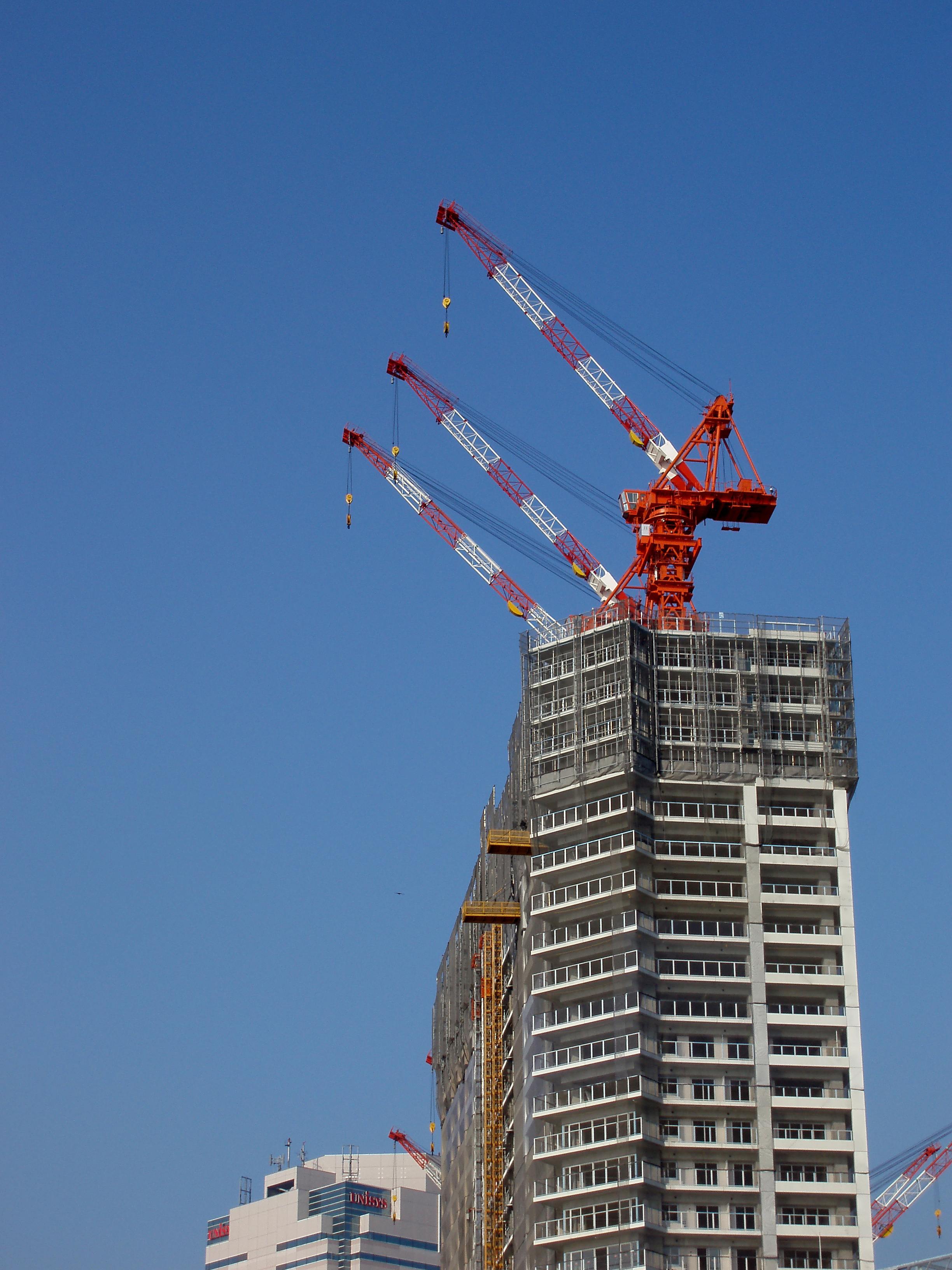 cranes on top of a building under construction in tokyo japan