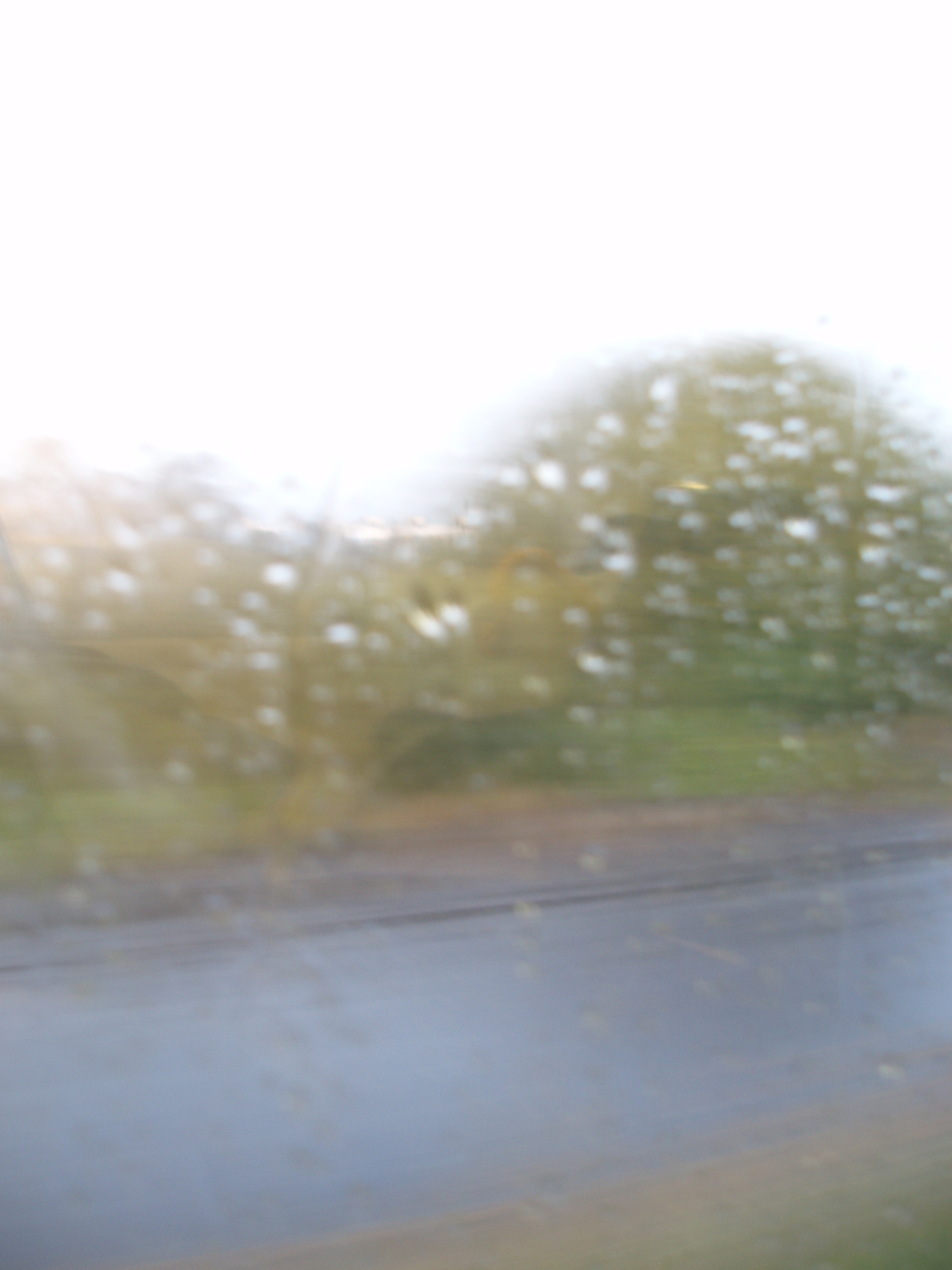 rain on a misted up window and a road outside