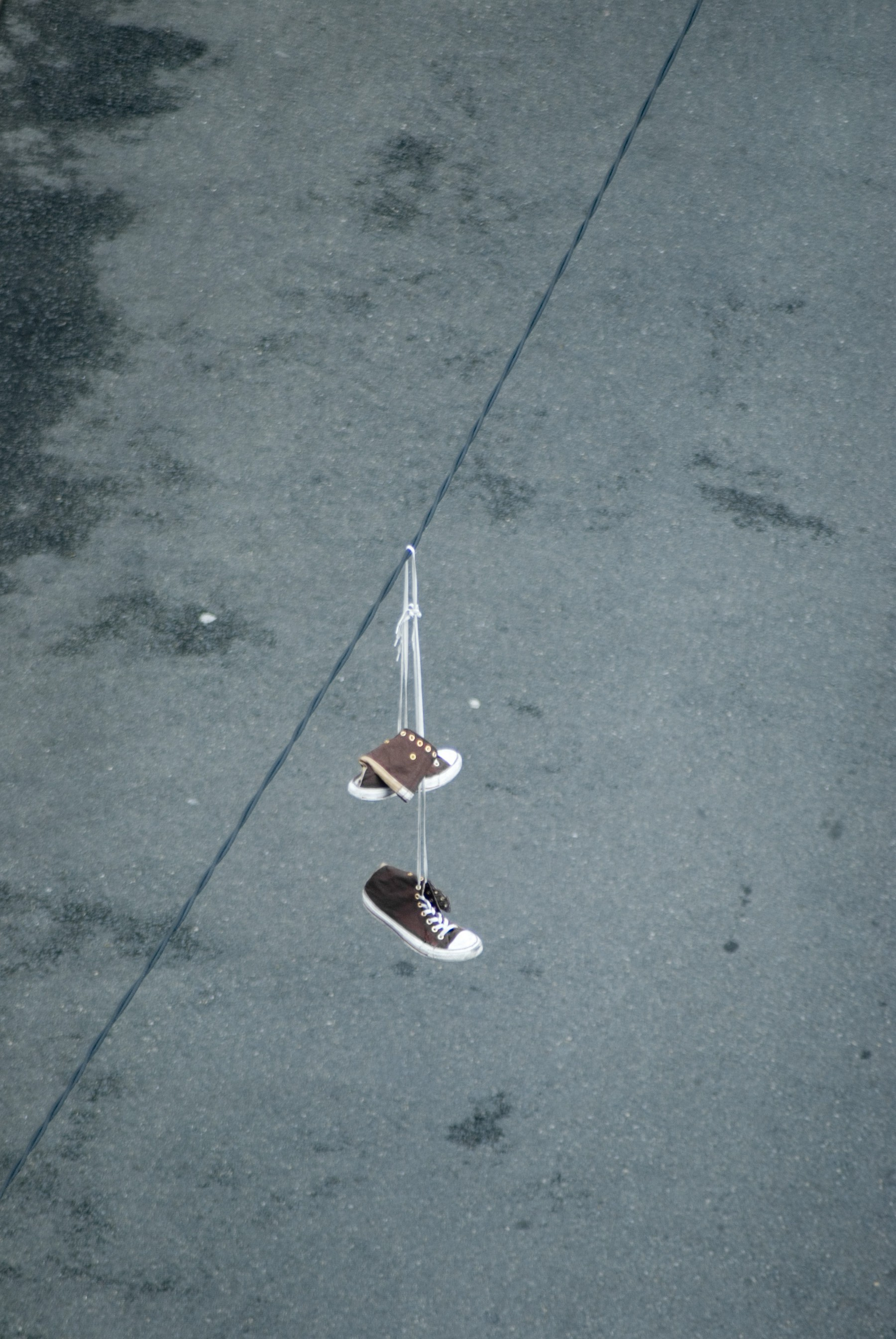 sneakers hanging on a power cable