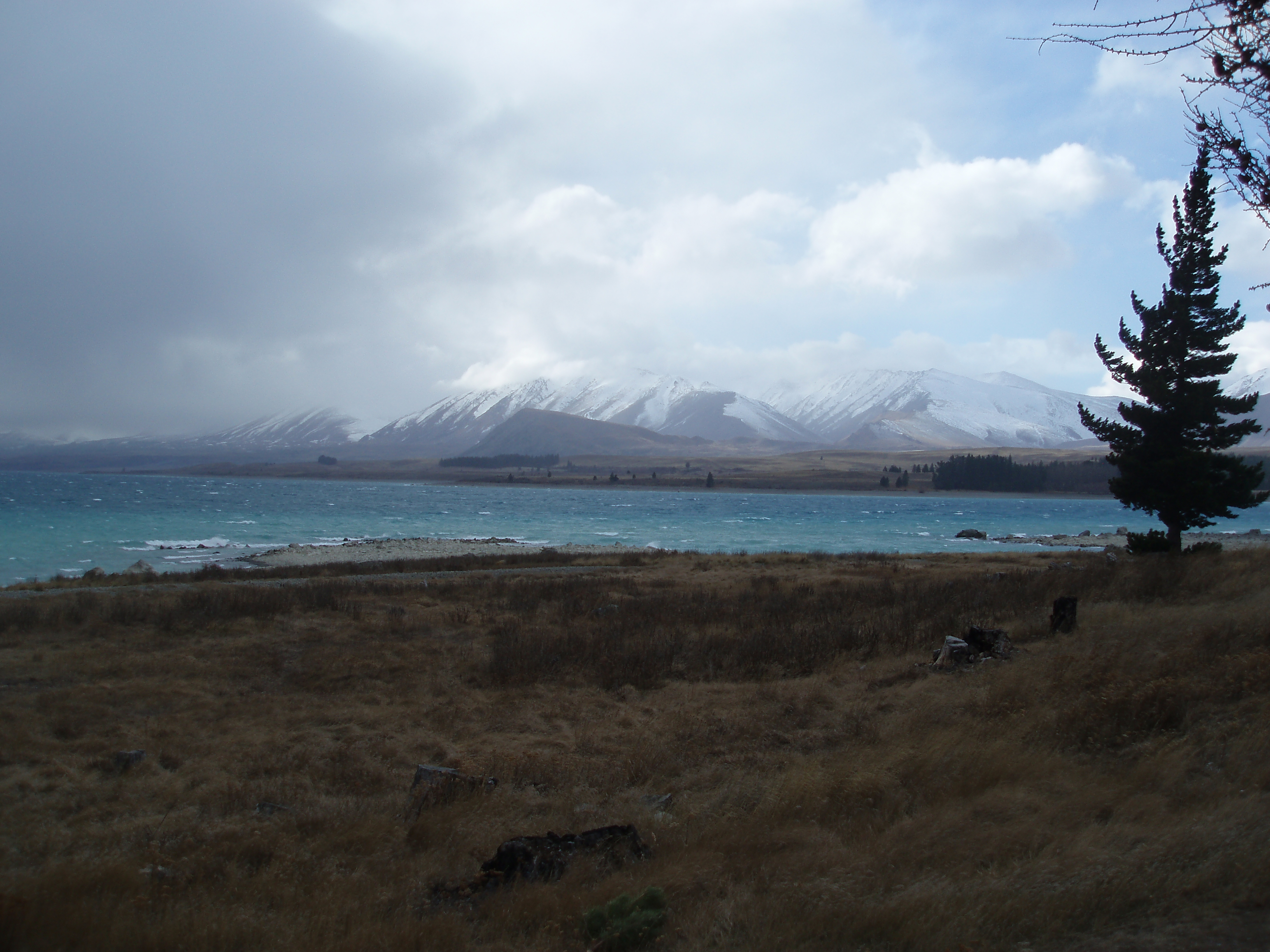 stormy day over a cyan glacial lake