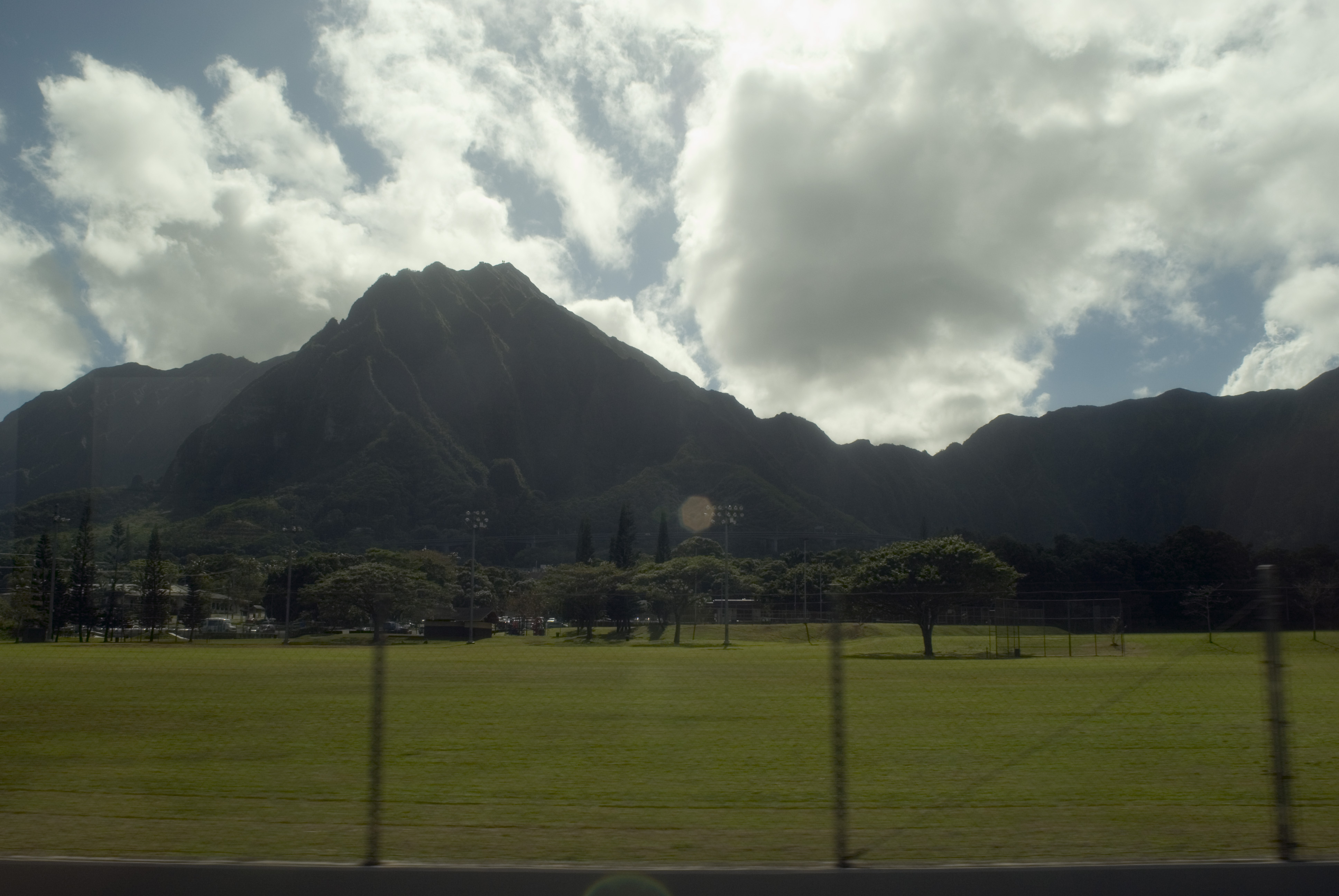 grungy through glass image with lens flare - hawaii mountains