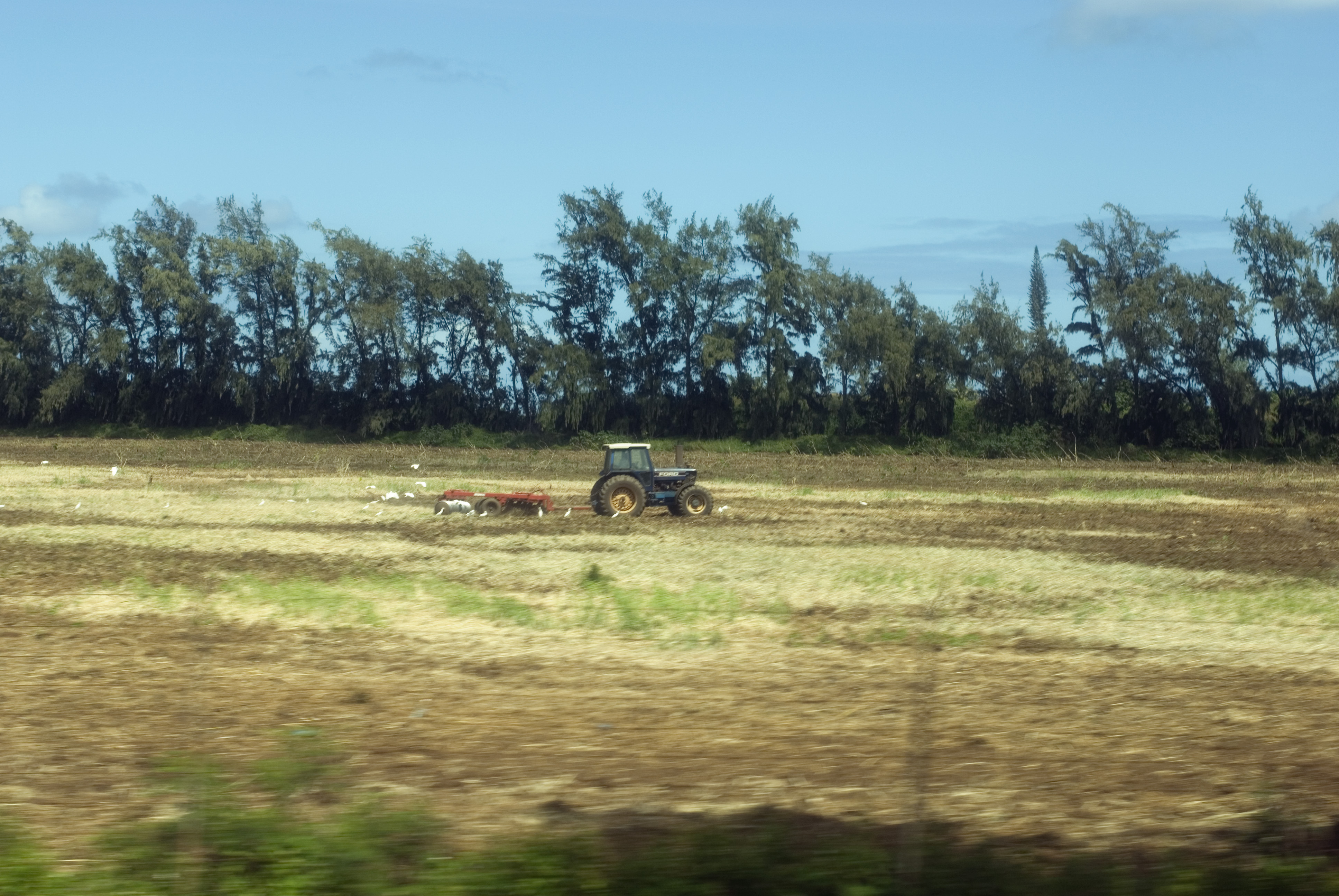 a tractor pulling a plough through a field