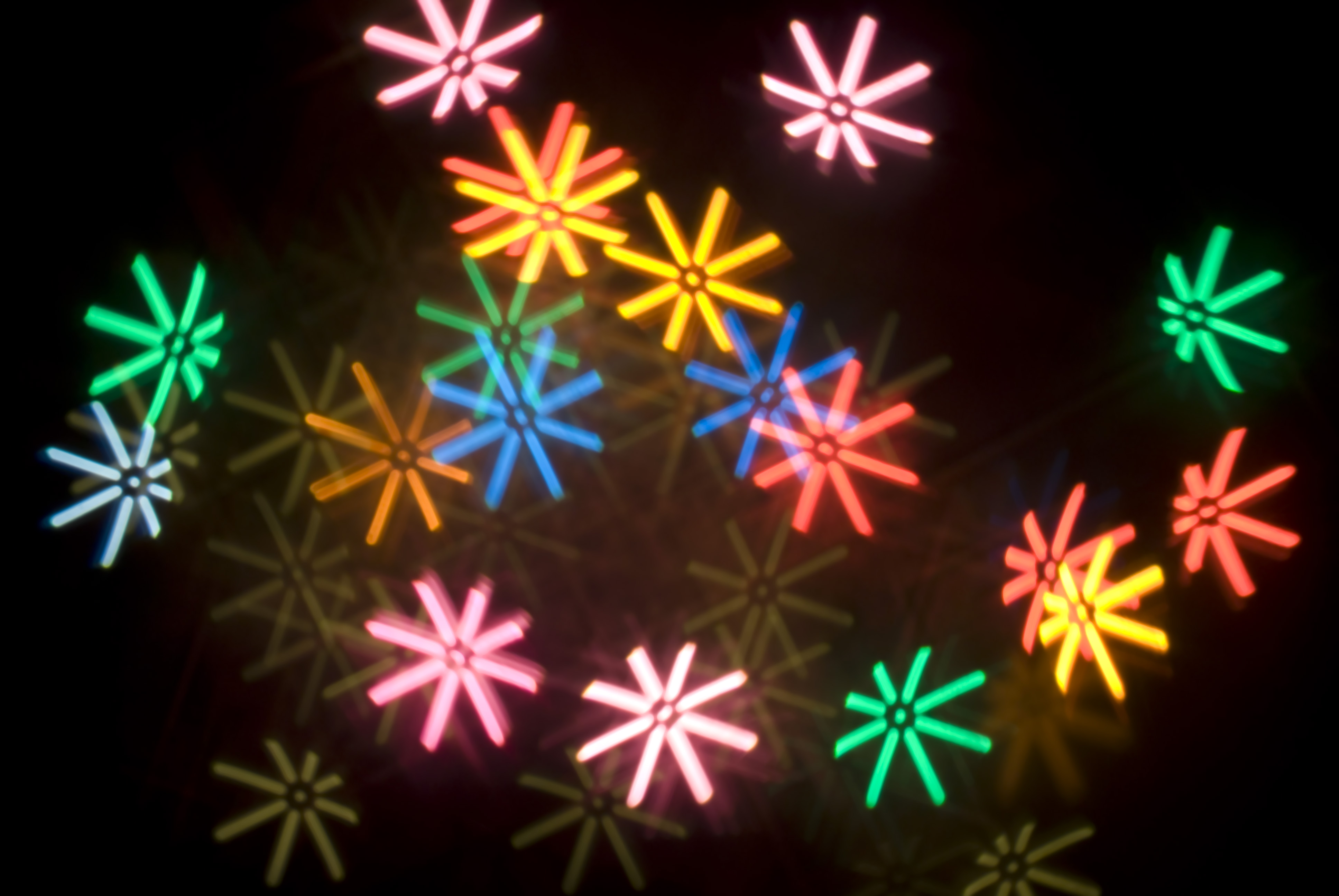 a pattern of colourful bokeh star shapes