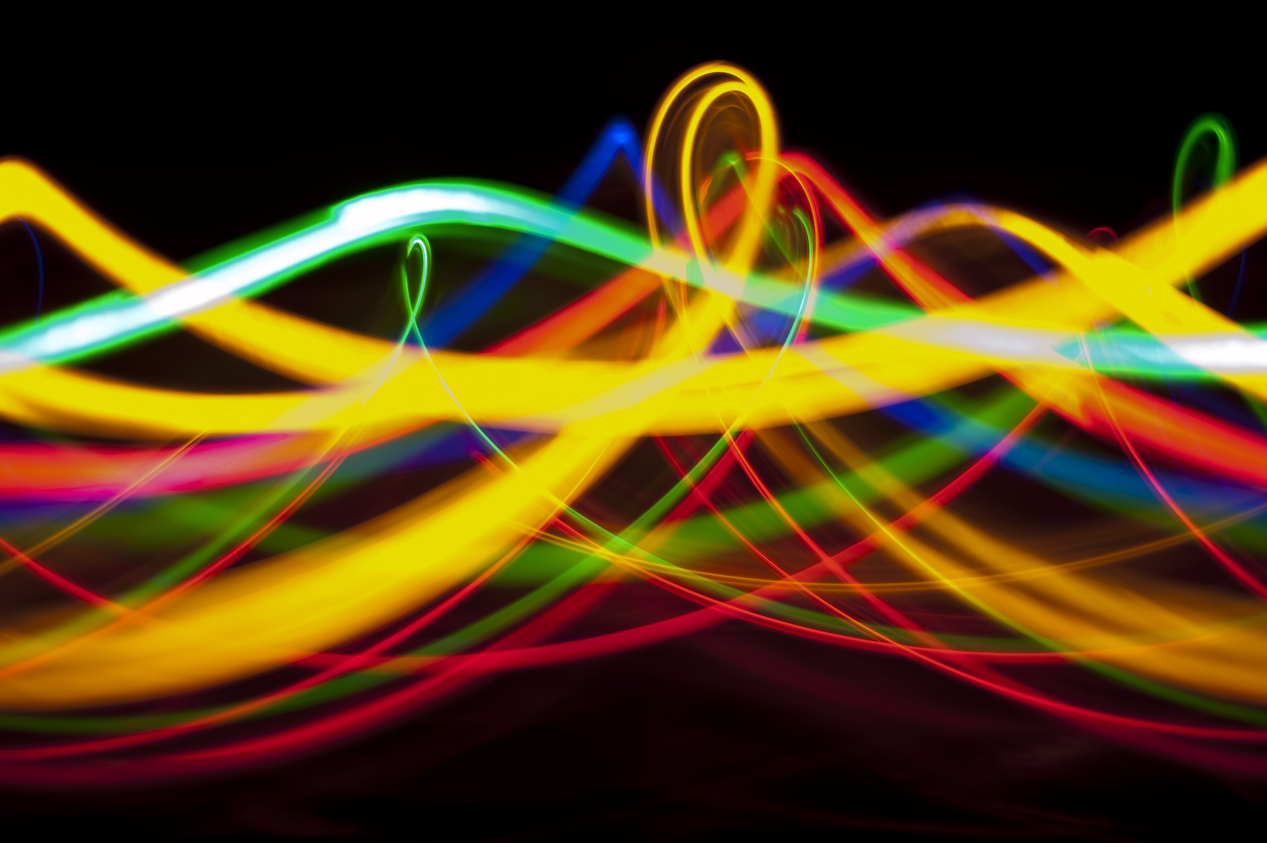 a vibrant corkscrew of colourful light trails on black background