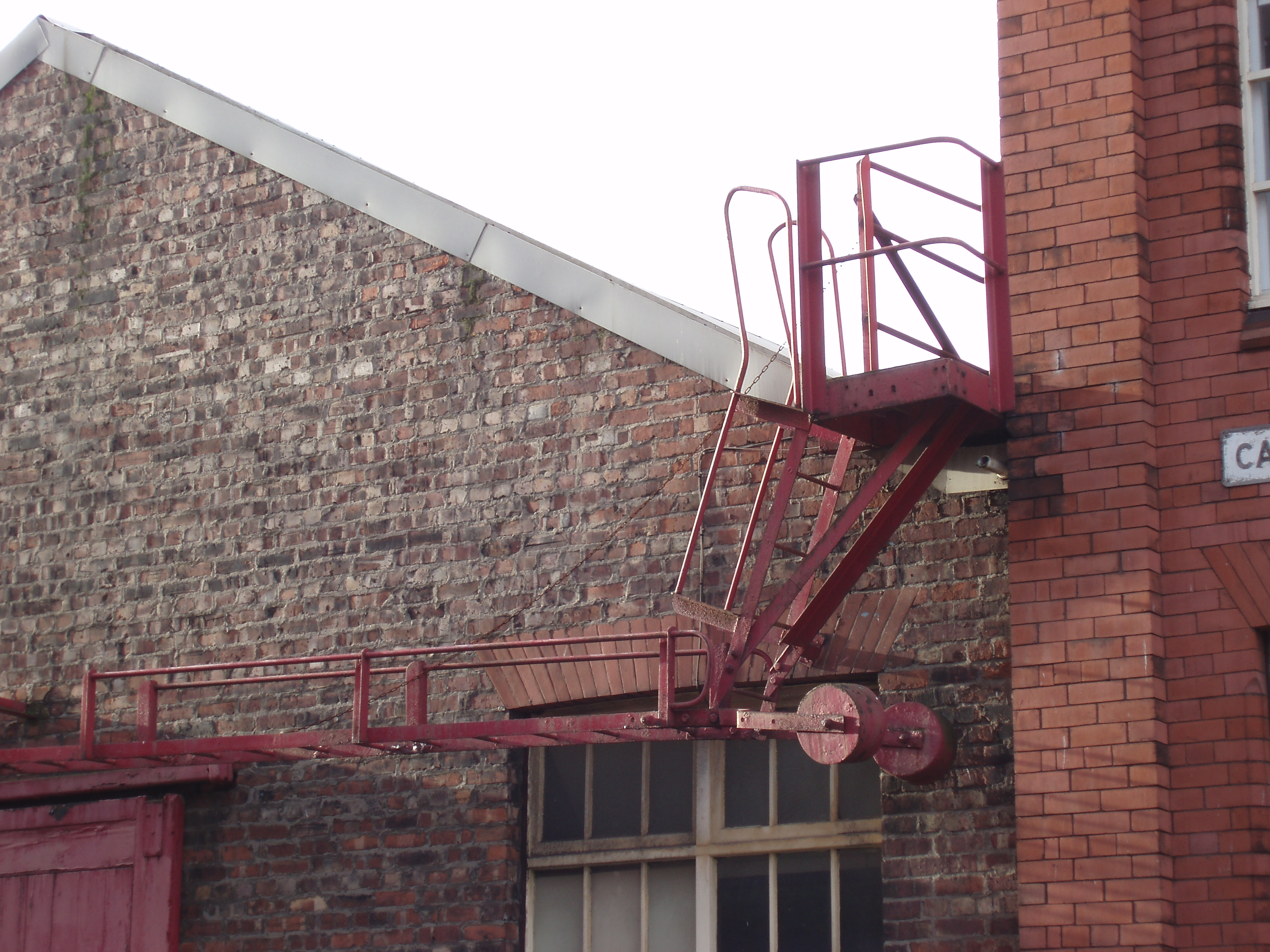 a metal firescape ladder on a old brick warehouse