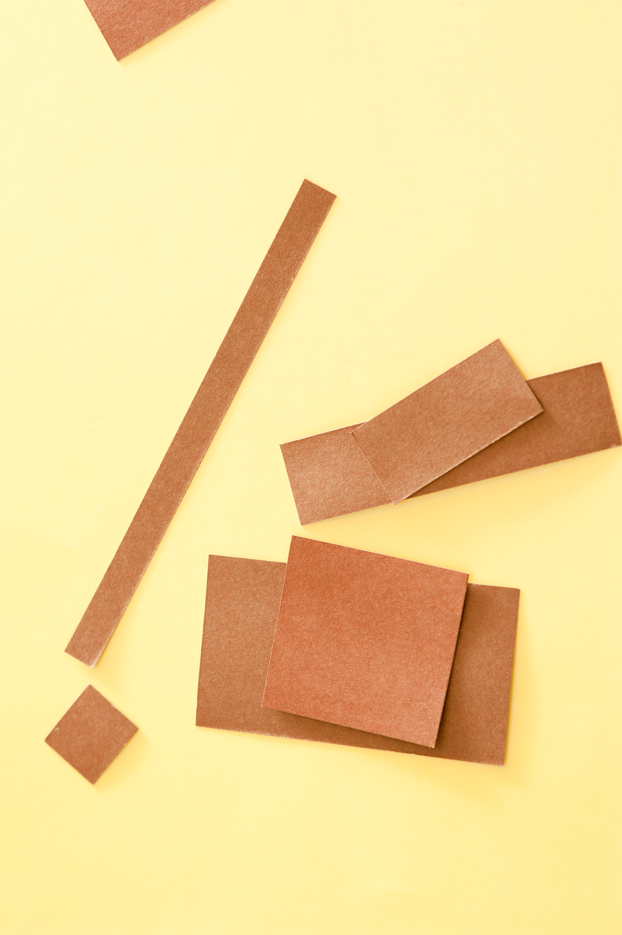 an assortment of overlapped brown paper rectangles on a yellow background