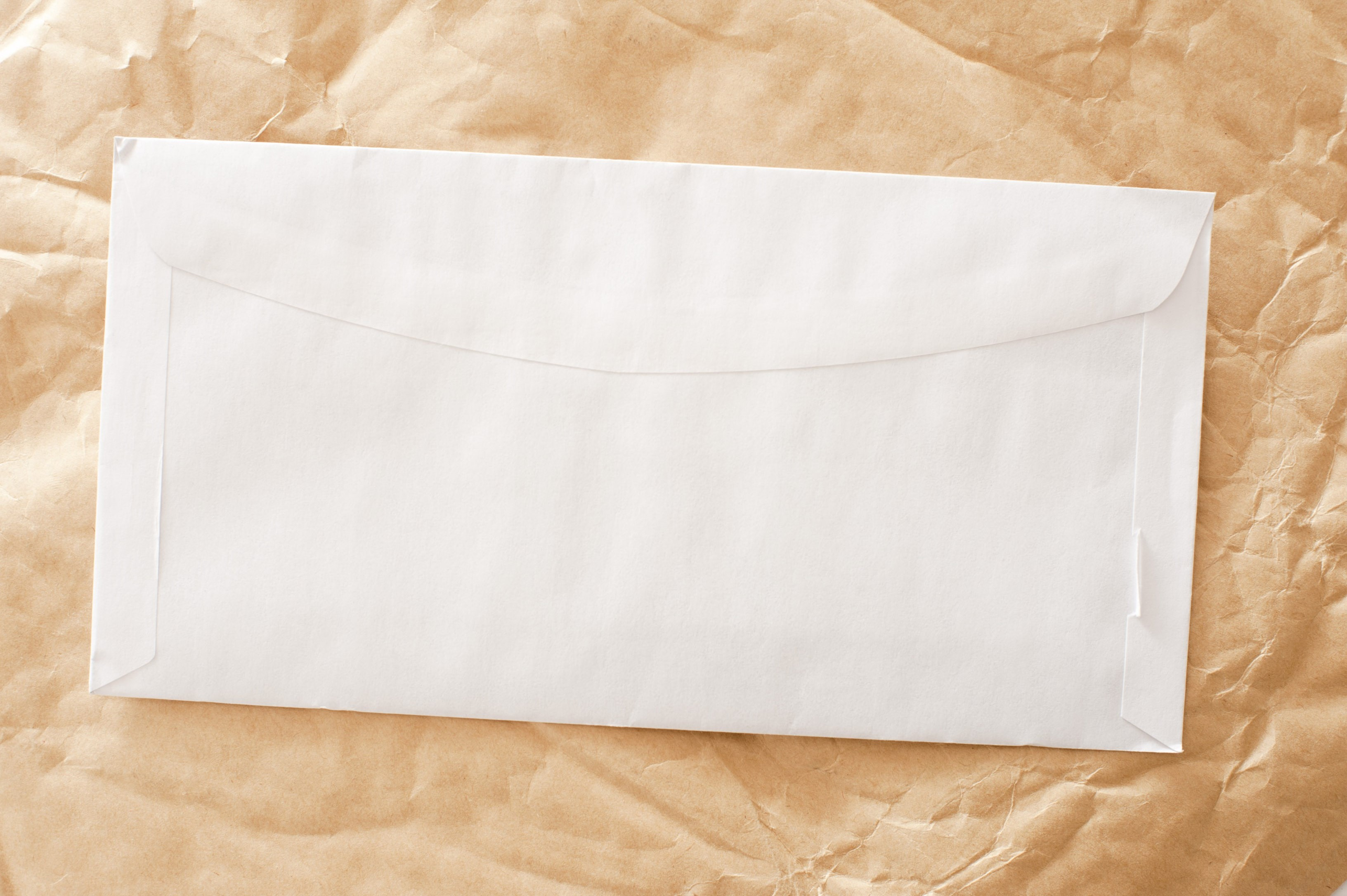 contrasting clean white envelope and a crumbled brown paper background