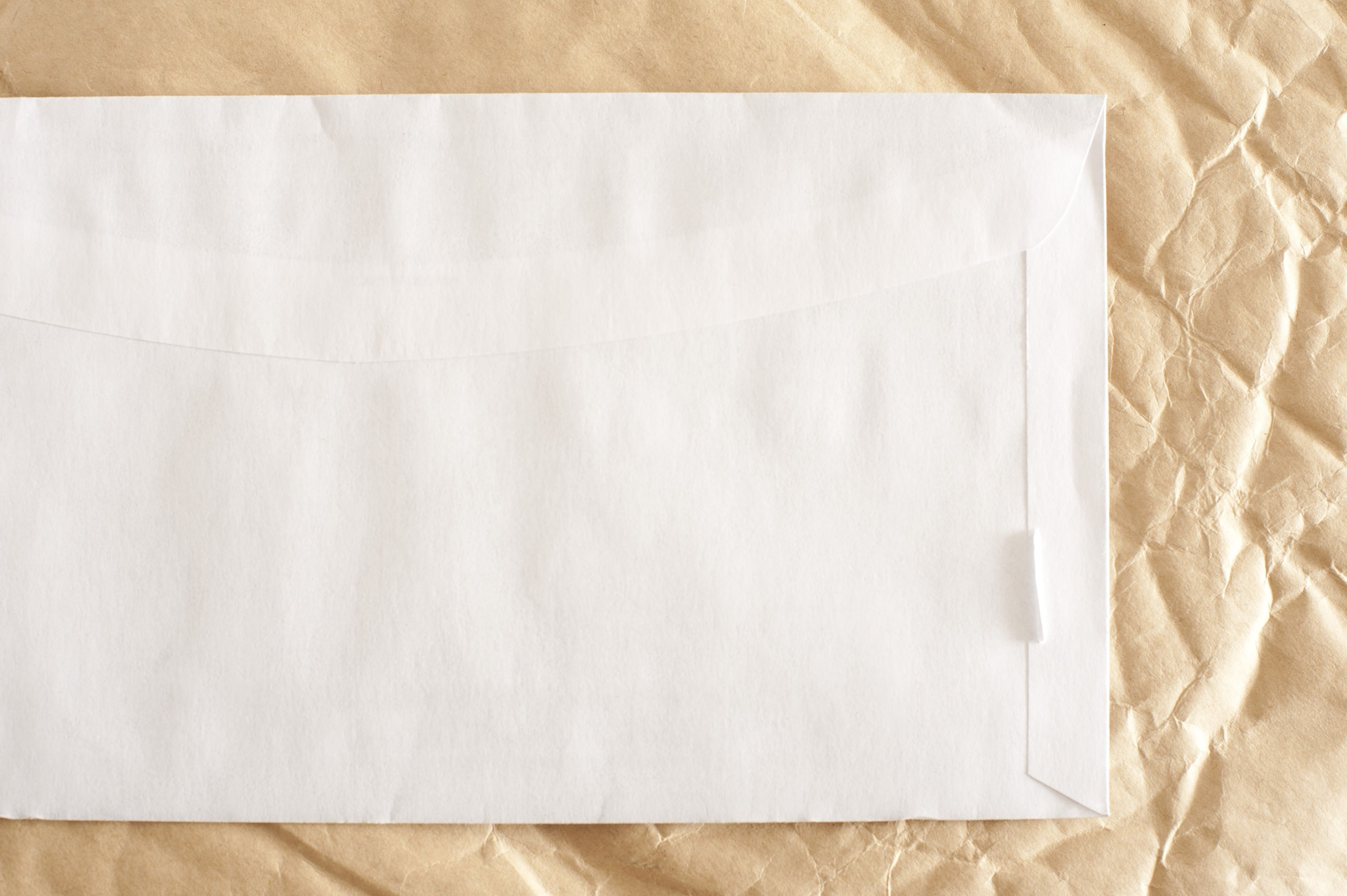 close up image of an envelope with space for text surrounded with crumpled paper